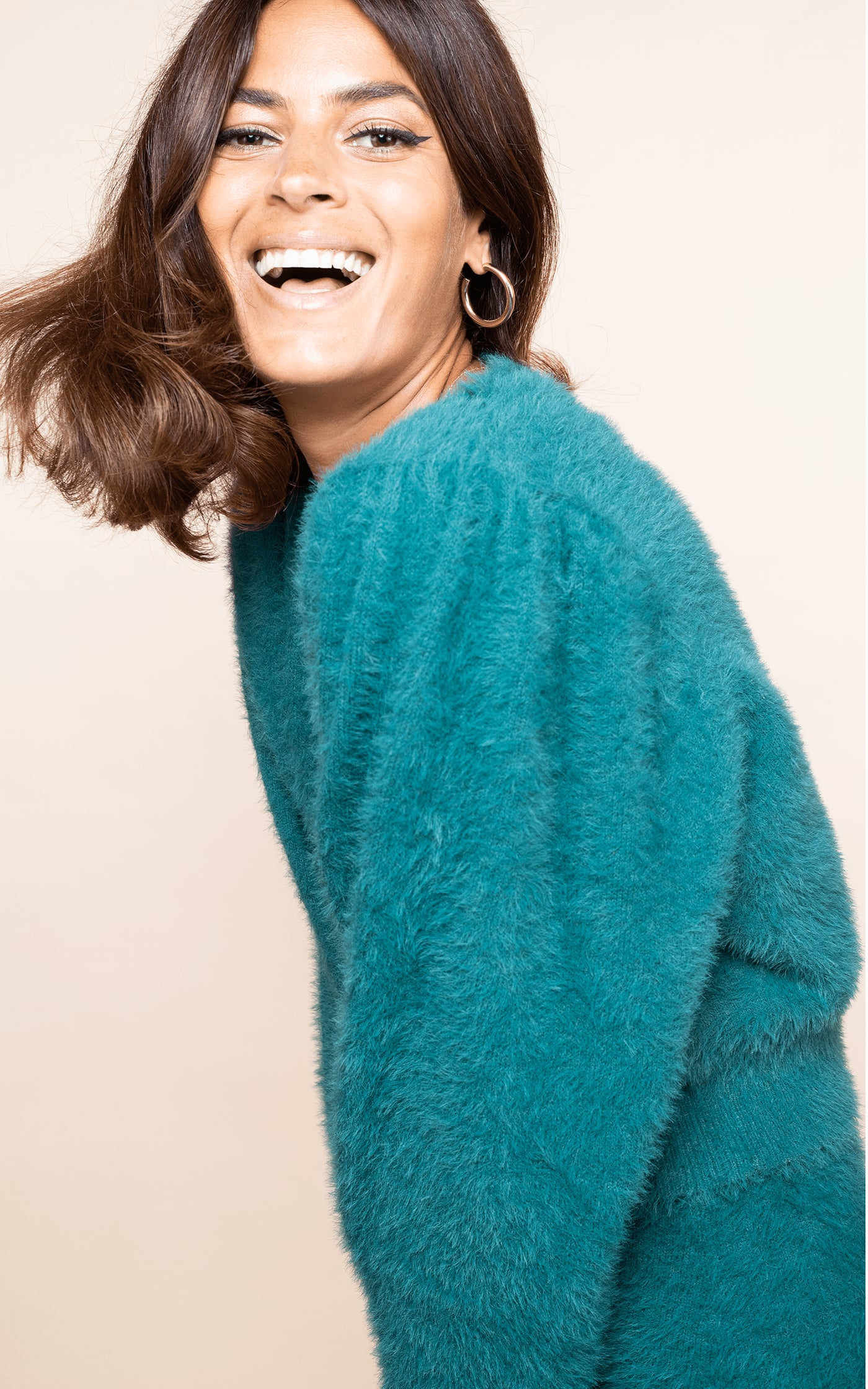 Close-up of Dancing Leopard model laughing wearing Ariana Cardigan in forest green