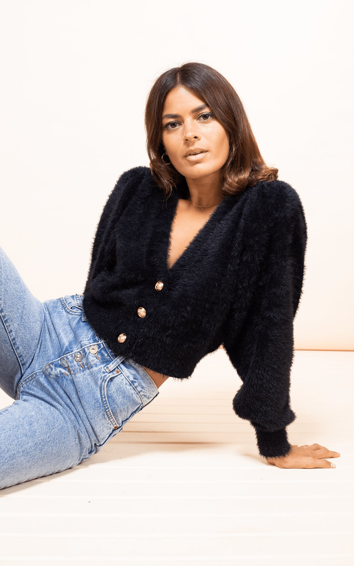Dancing Leopard model sits on floor wearing Ariana Cardigan in Black with jeans