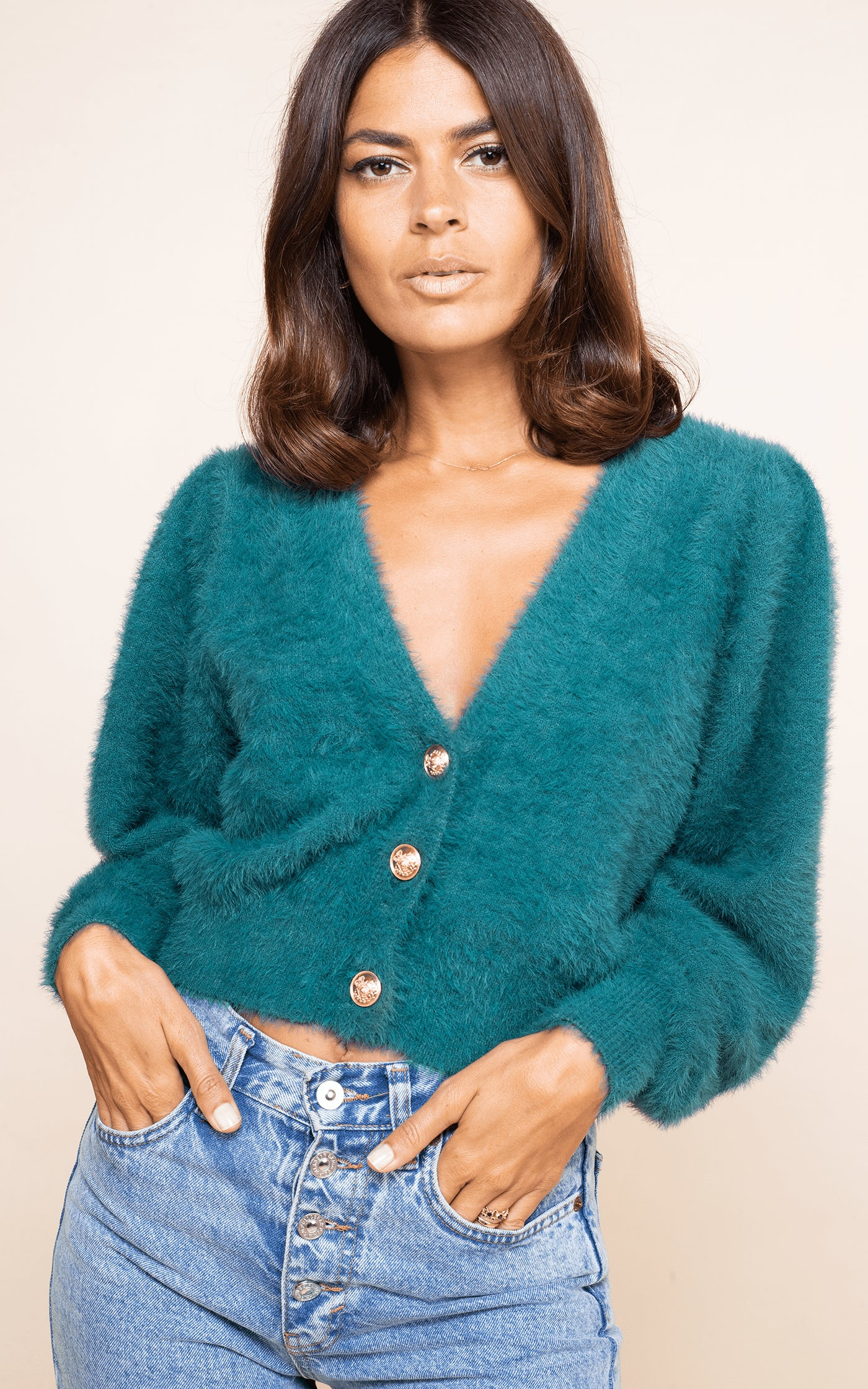 Close-up of Dancing Leopard model wearing Ariana Cardigan in forest green with jeans