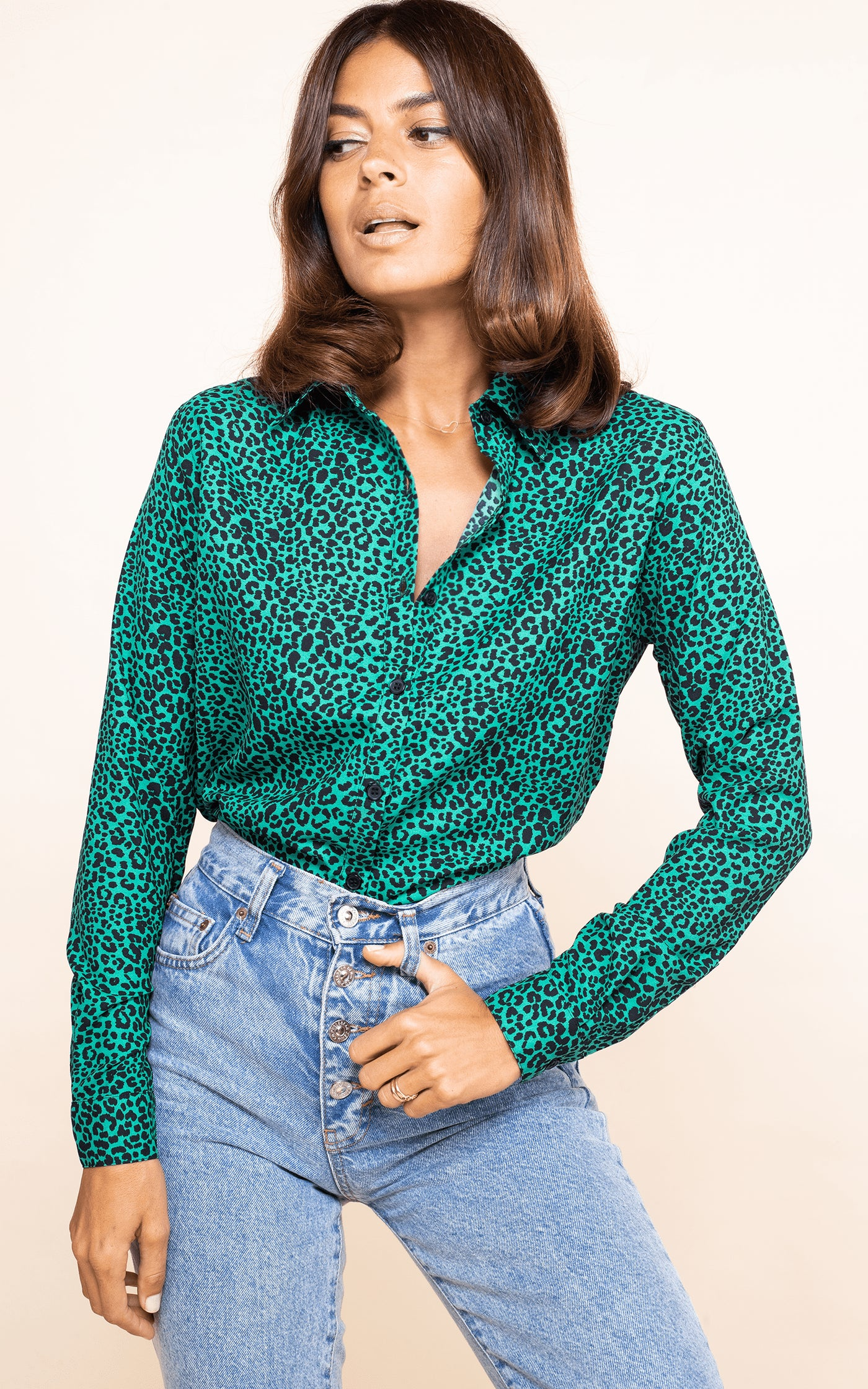 Dancing Leopard model looks sideways wearing San Diego Shirt in green leopard print with blue jeans