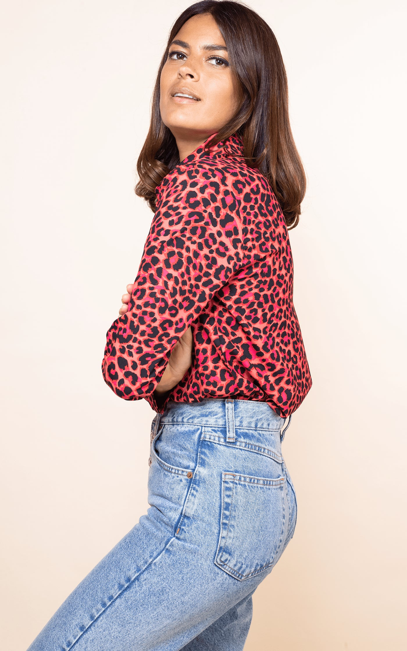 Dancing Leopard model crossed arms and faces sideways wearing San Diego Shirt in red leopard with jeans