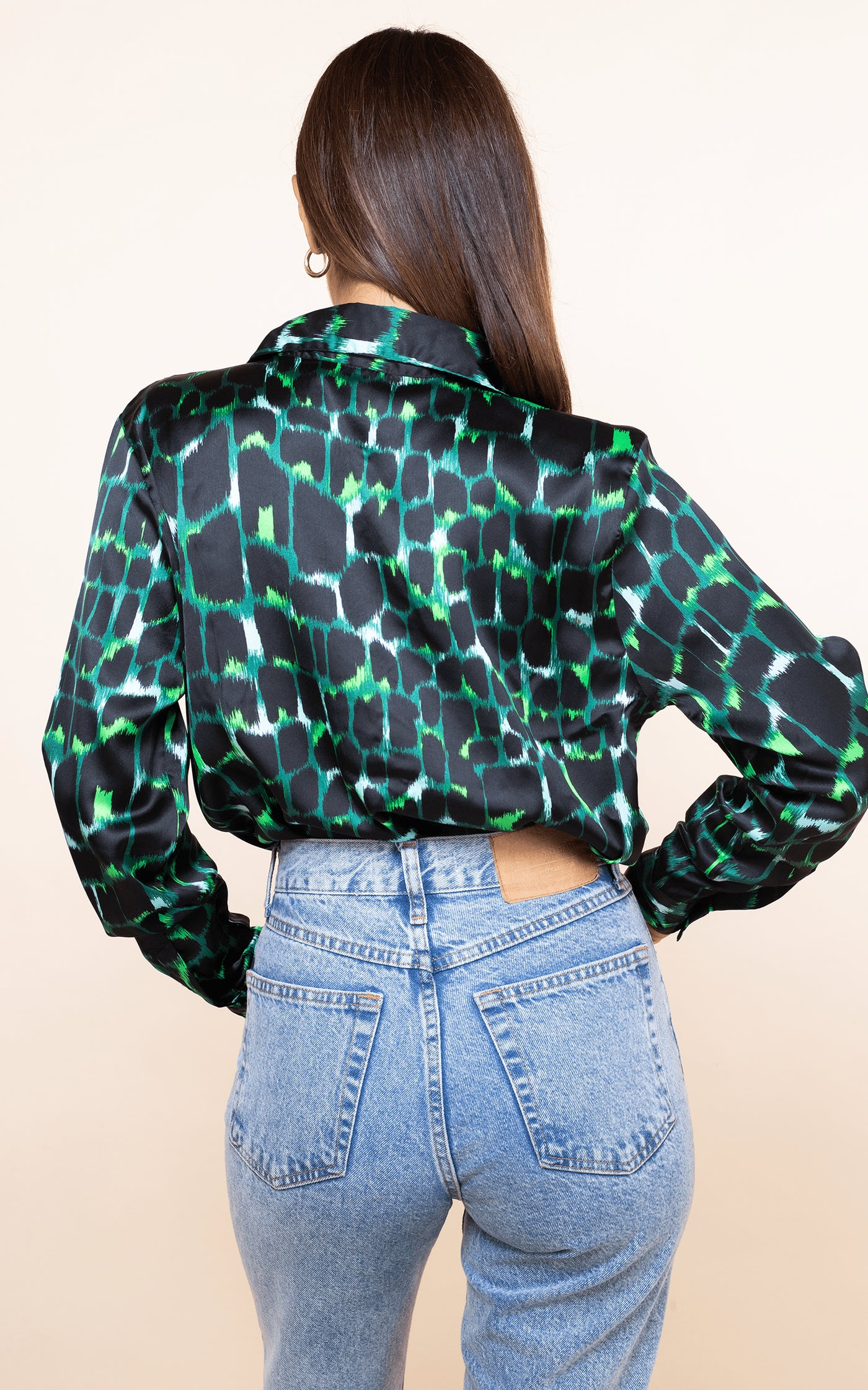 Dancing Leopard model faces backwards with hand on hip wearing San Diego Shirt in green alligator print with jeans