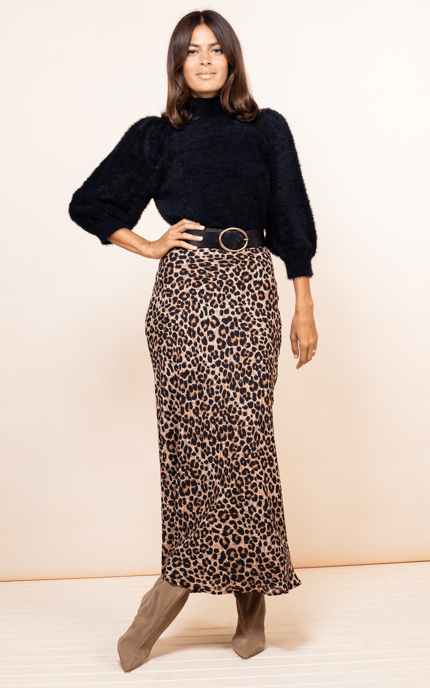 Dancing Leopard model faces forward wearing Sophie Skirt in Rich Leopard print with black fluffy jumper with hand on hip