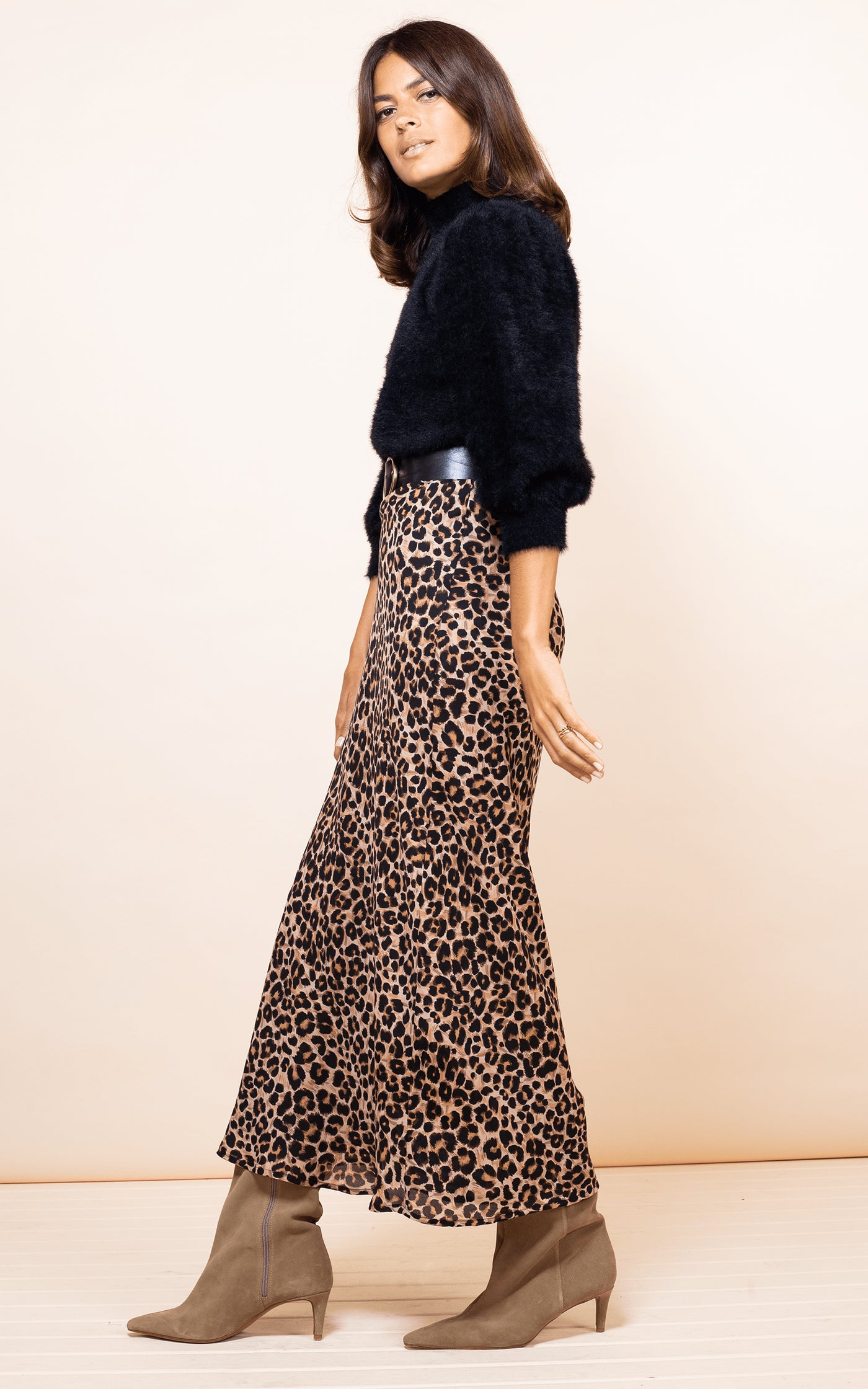 Dancing Leopard model walks forwards wearing Sophie Skirt in leopard print with black fluffy jumper and boots