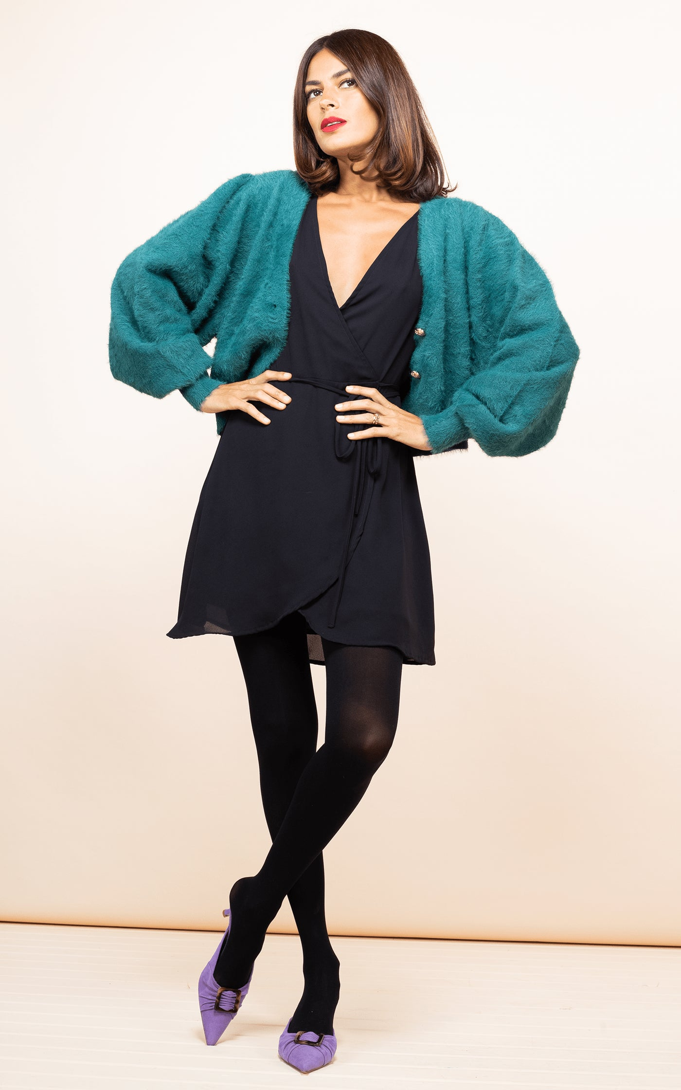 Dancing Leopard model faces forwards wearing Teagan Mini Dress in Black with green cardigan