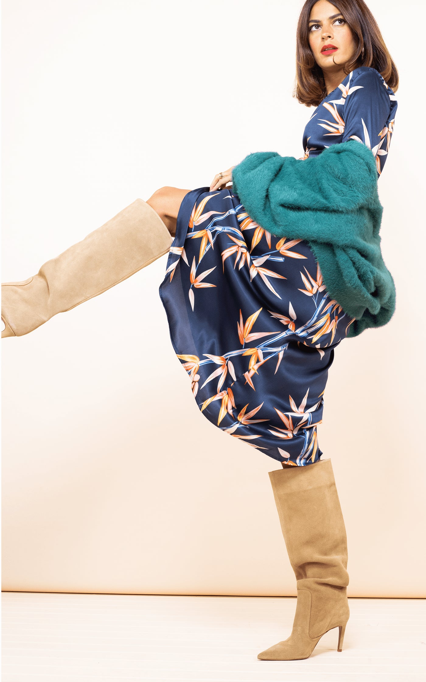 Dancing Leopard model faces side-on and kicks leg up wearing Yondal Dress in Bamboo with green cardigan and boots