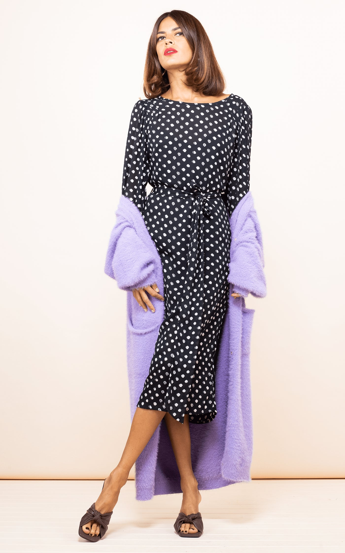 Dancing Leopard model faces forwards wearing Sabina Dress in Black Dotty with purple cardigan