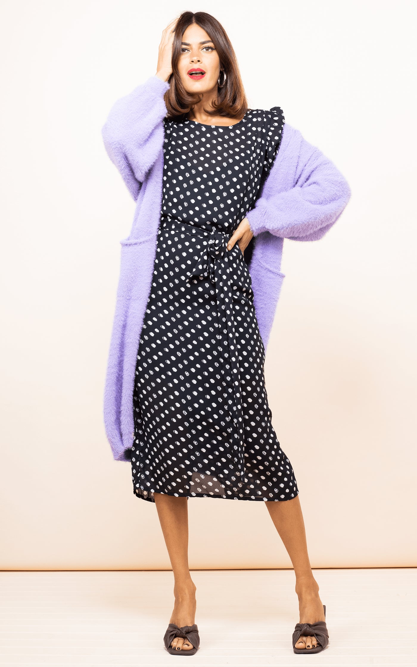 Dancing Leopard model faces forwards with hand on head wearing Sabina Dress in Black Dotty with purple cardigan