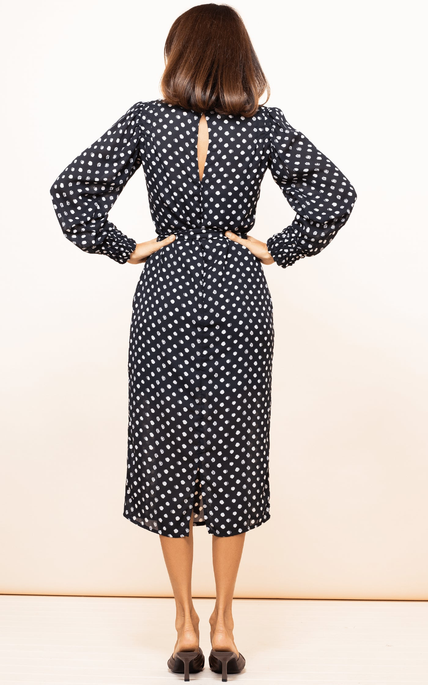 Dancing Leopard model faces backwards with hands on hips wearing Sabina Dress in Black Dotty
