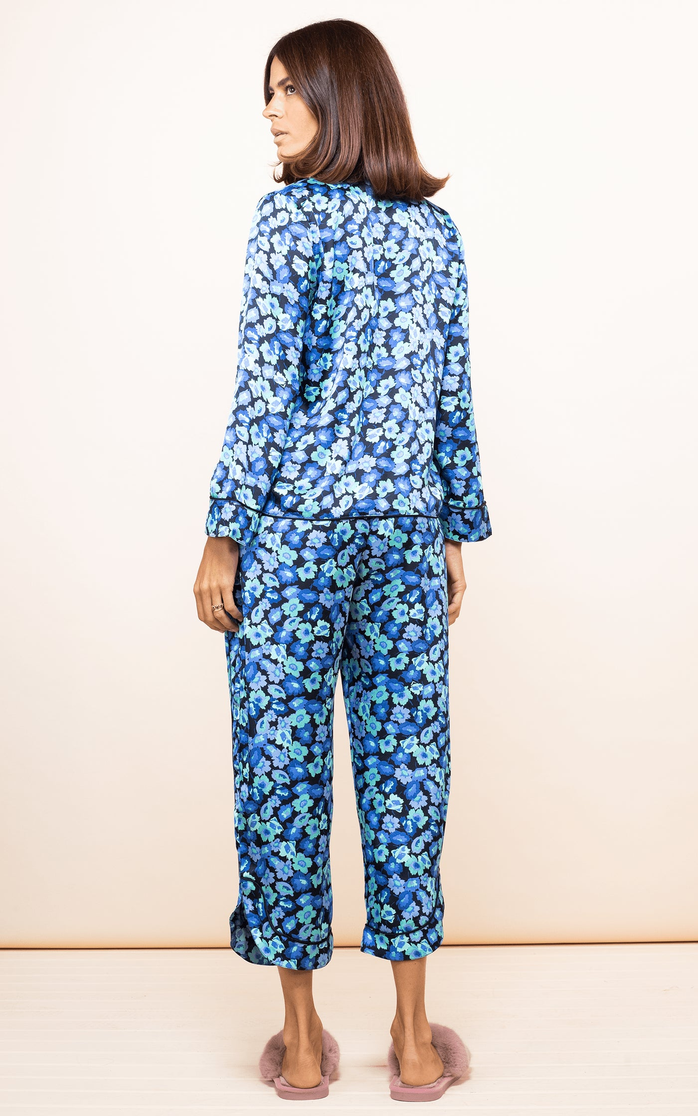 Dancing Leopard model faces backwards wearing Enya PJ Set in 50s-inspired blue floral print with slippers