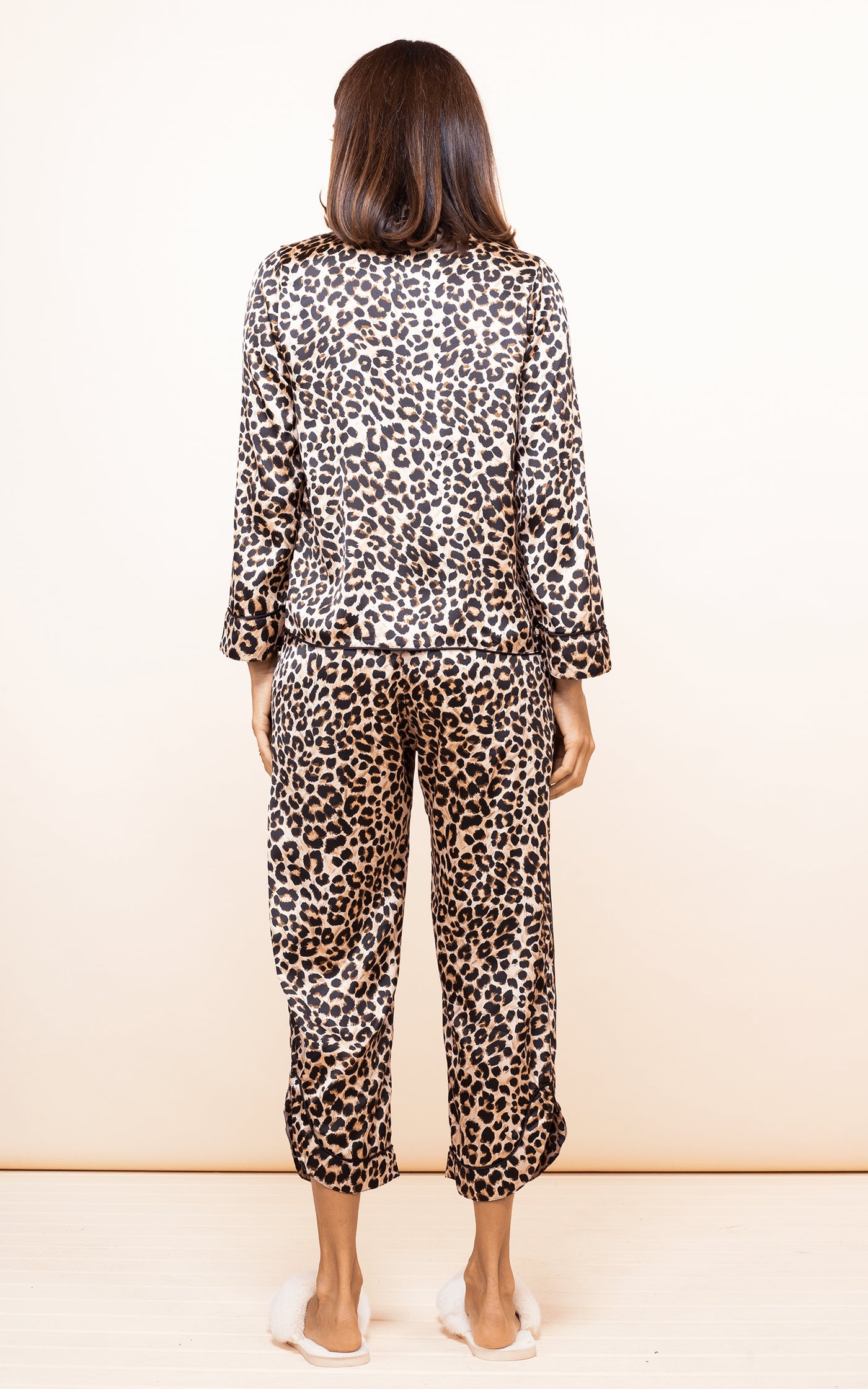 Dancing Leopard model faces backwards wearing Enya PJ Set in Rich Leopard print and slippers