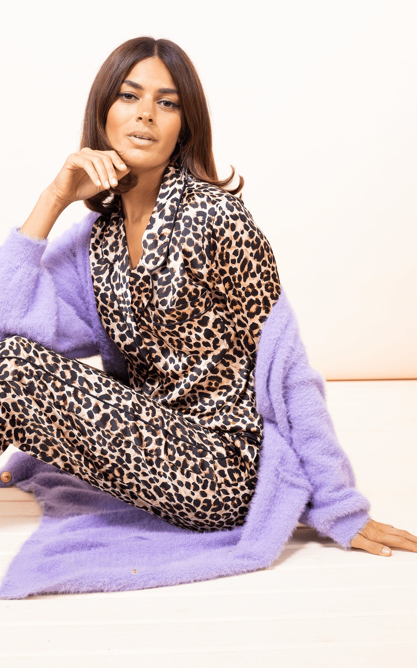 Dancing Leopard model sits on floor wearing Enya PJ Set in Rich Leopard print with purple cardigan and slippers