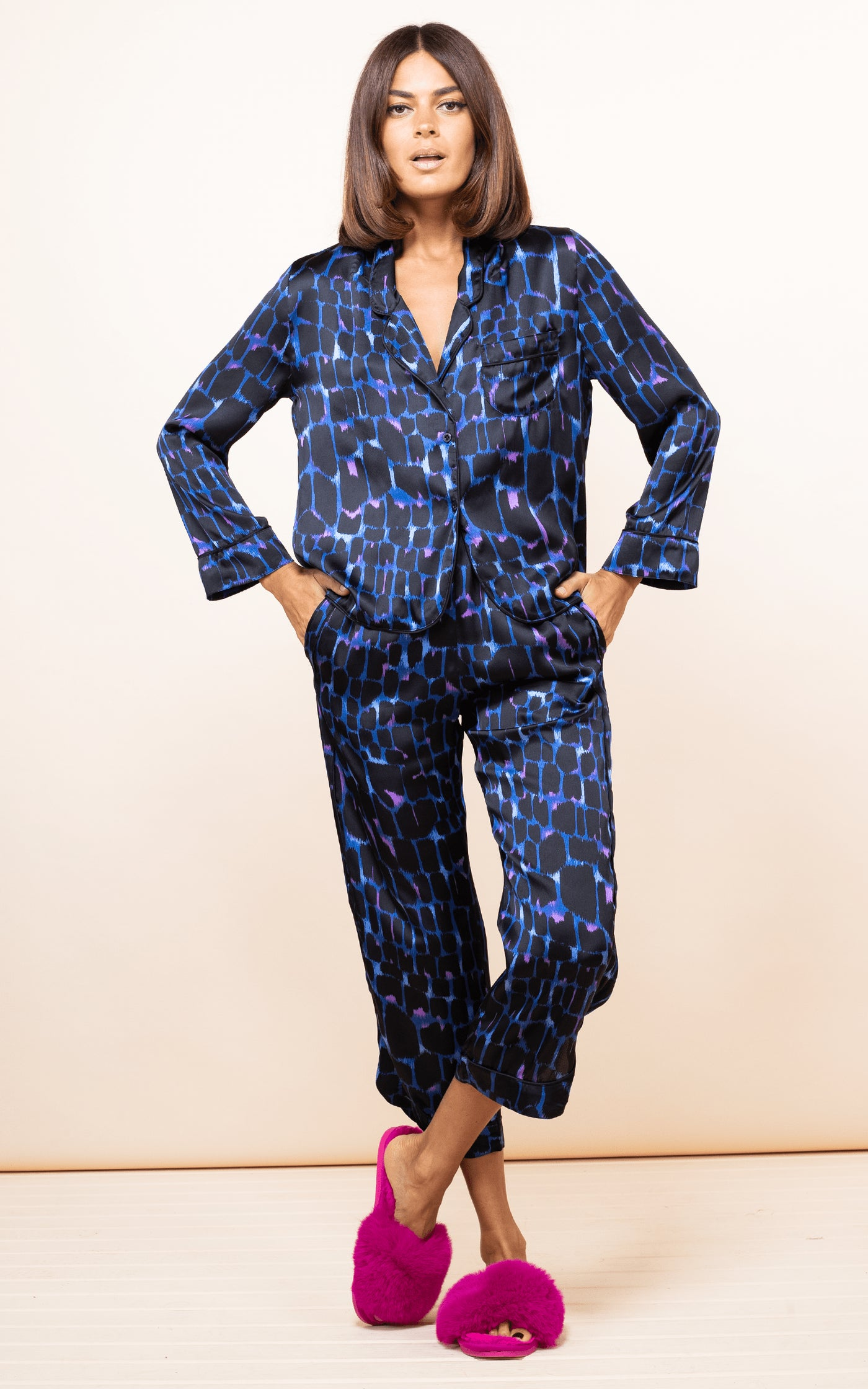 Dancing Leopard model faces forward with hands in pockets wearing Enya PJ Set in blue alligator print with slippers