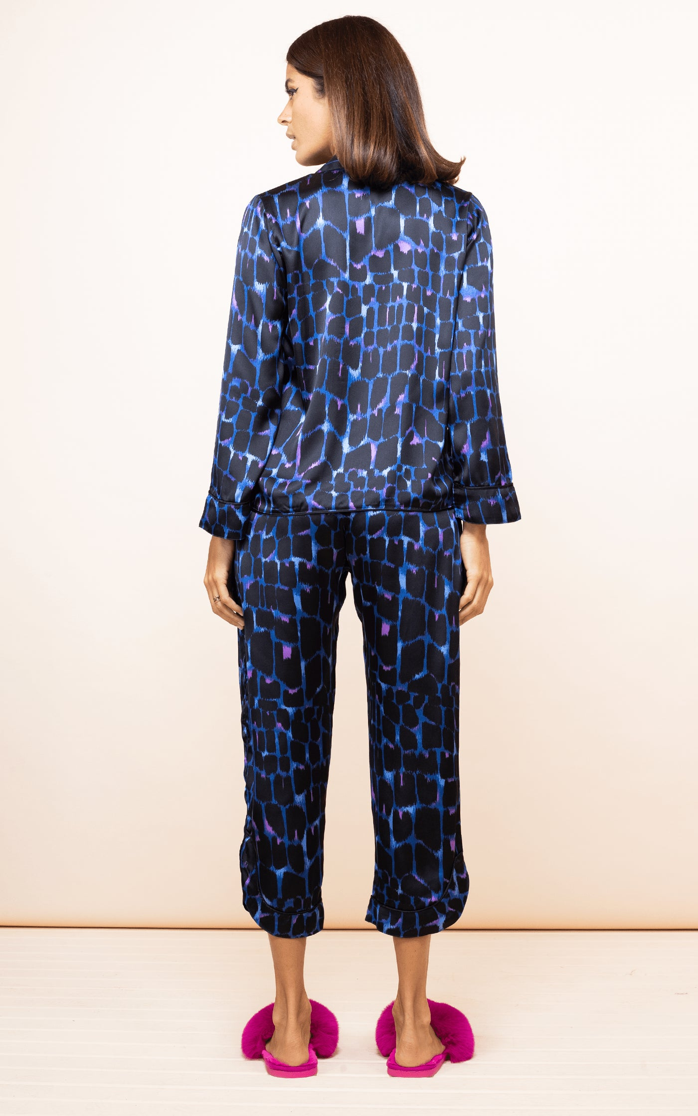 Dancing Leopard model faces backwards wearing Enya PJ Set in blue alligator print with slippers