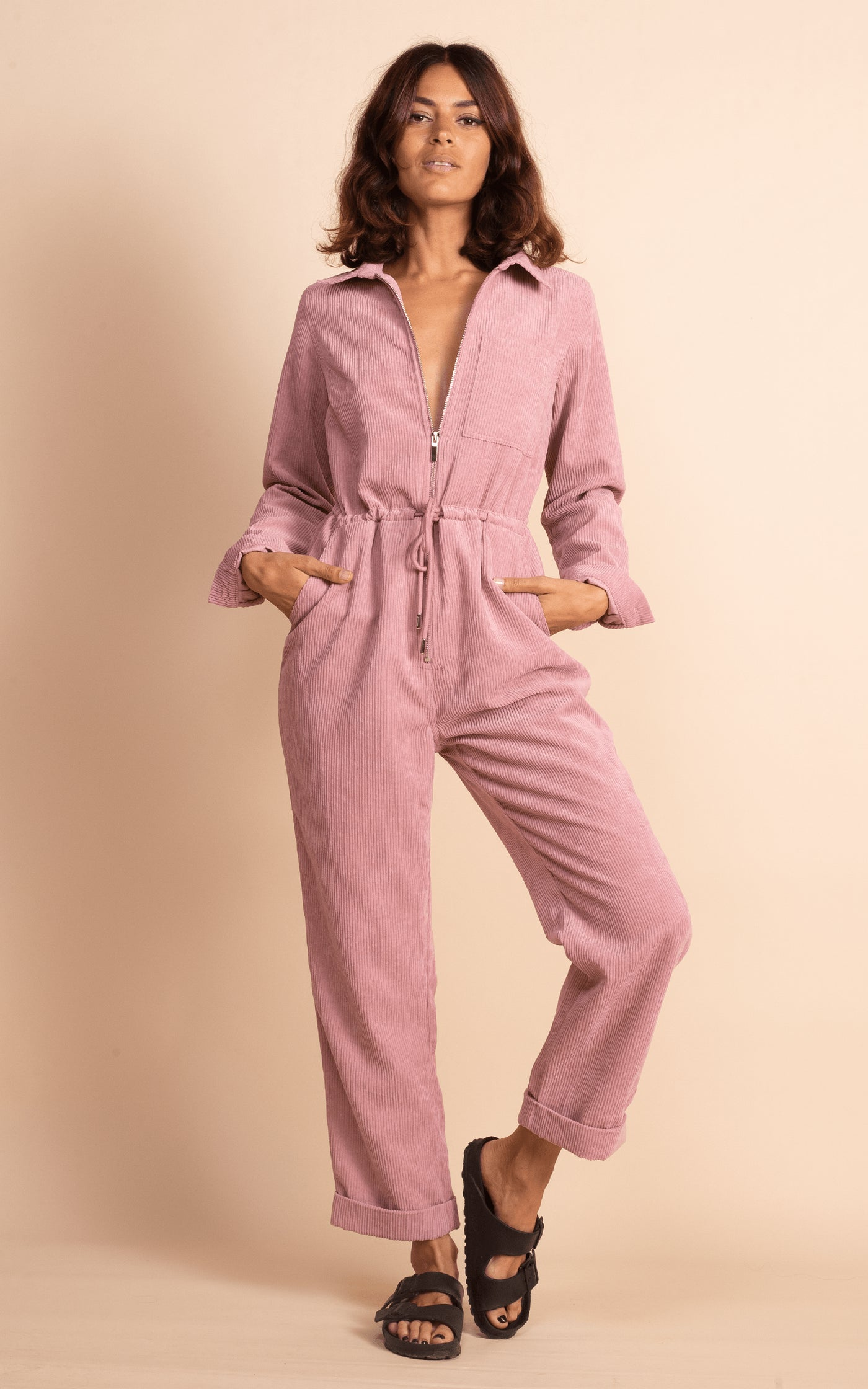 Dancing Leopard model faces forwards wearing Blaze Boilersuit in Rose Pink with sandals