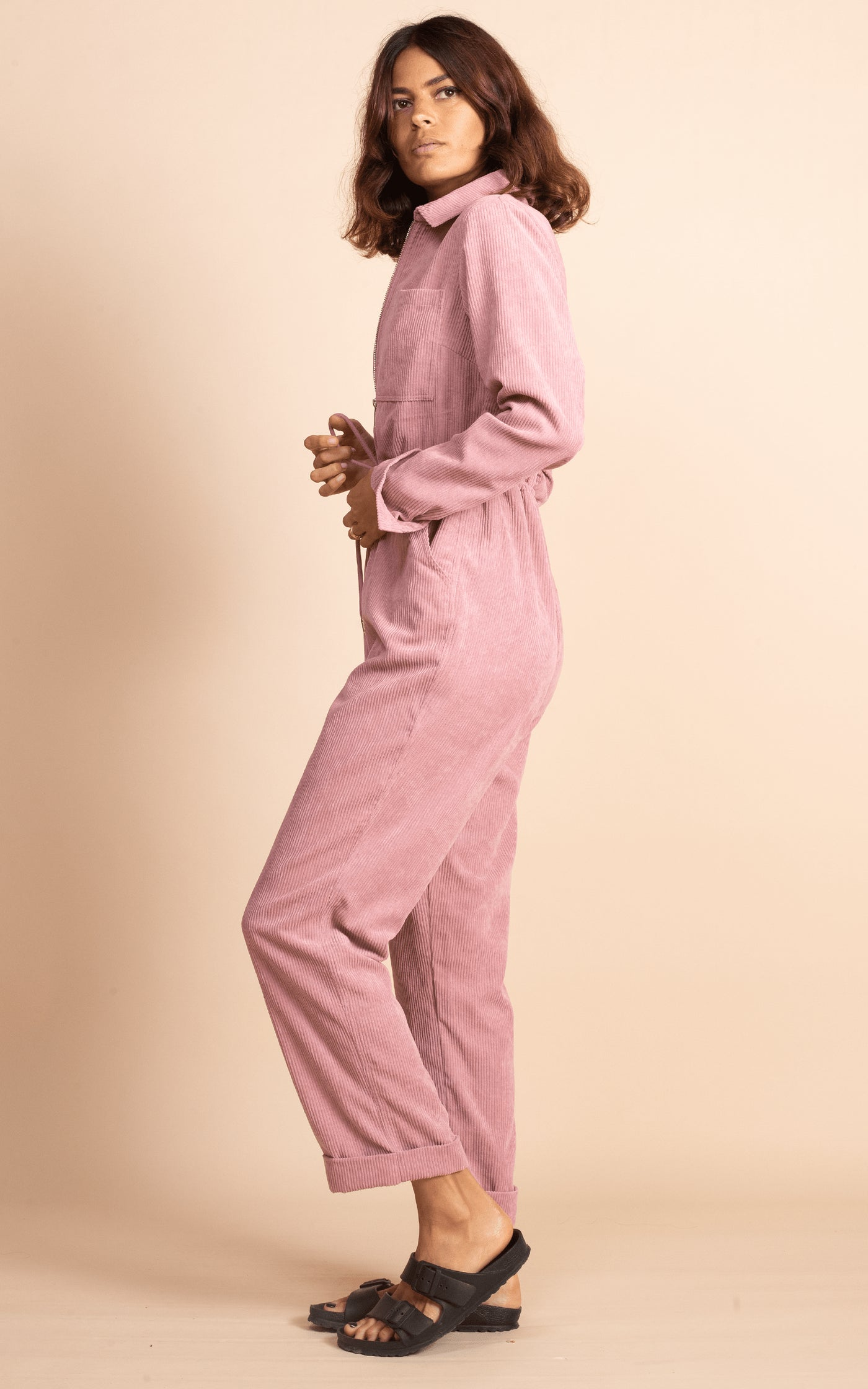 Dancing Leopard model faces side-on wearing Blaze Boilersuit in Rose Pink with sandals