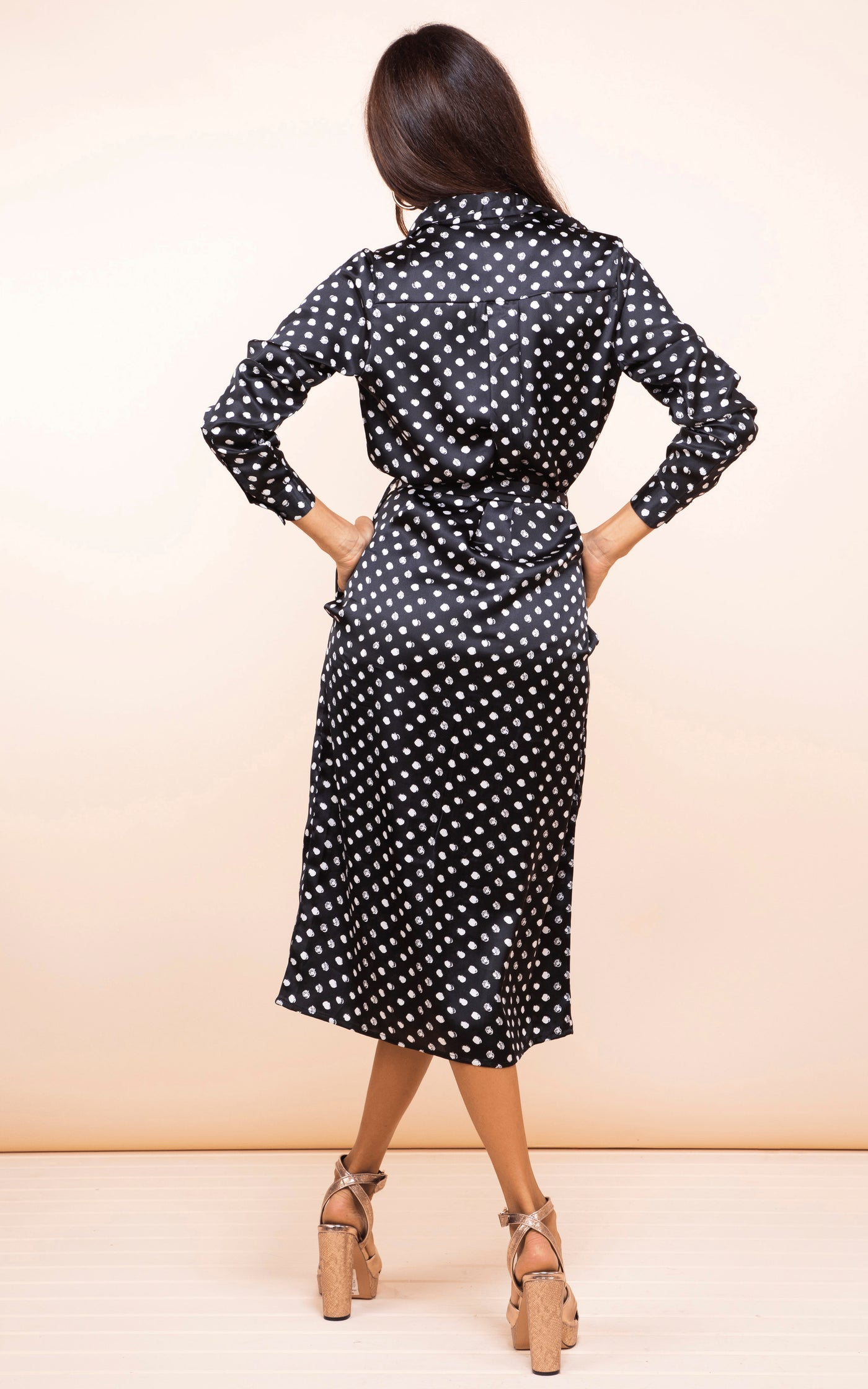 Backward-facing model wears Dancing Leopard Hadiba Midi Shirt Dress in black dotty print
