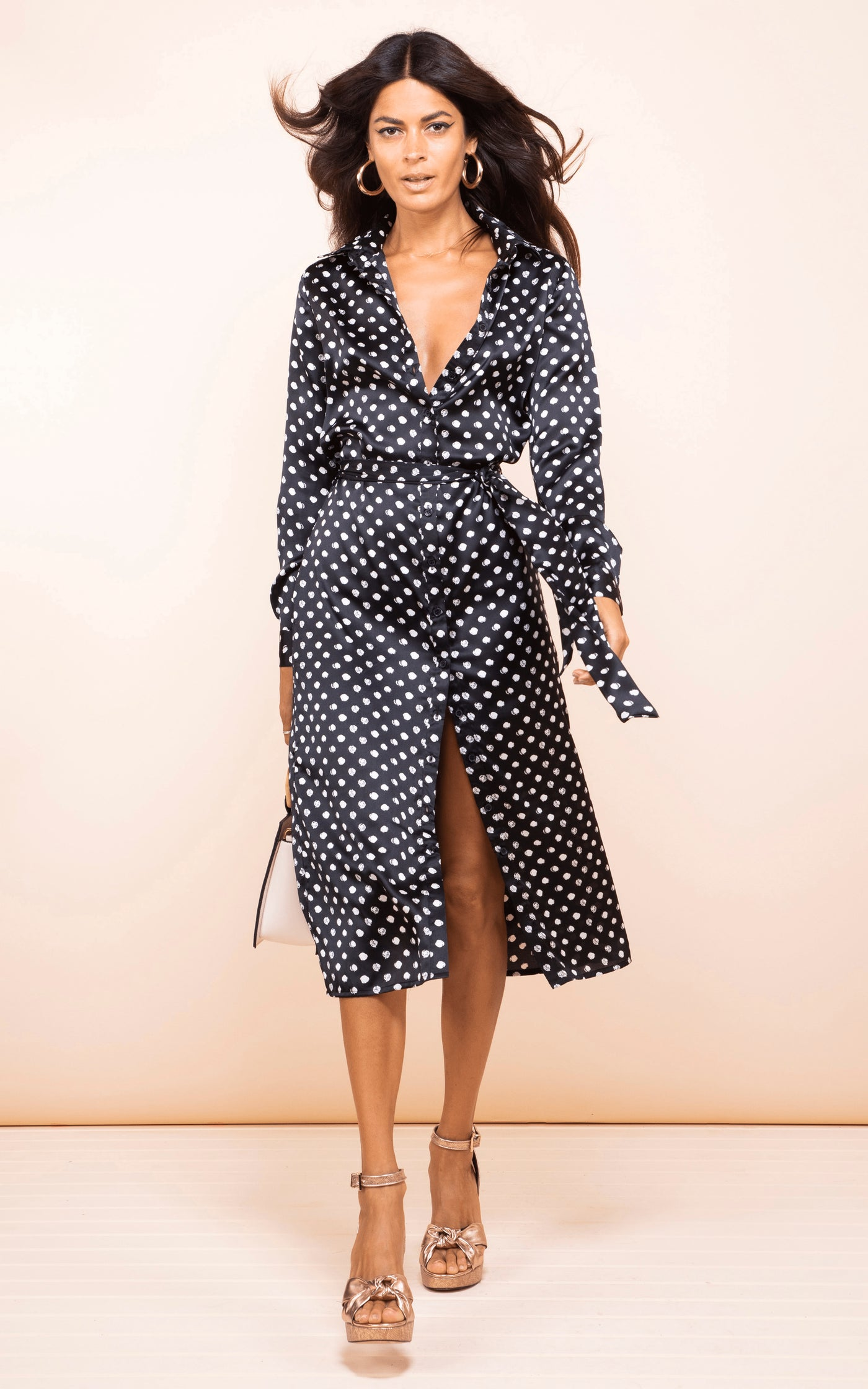 Dancing Leopard model walks forward wearing Hadiba Midi Shirt Dress in black dotty print