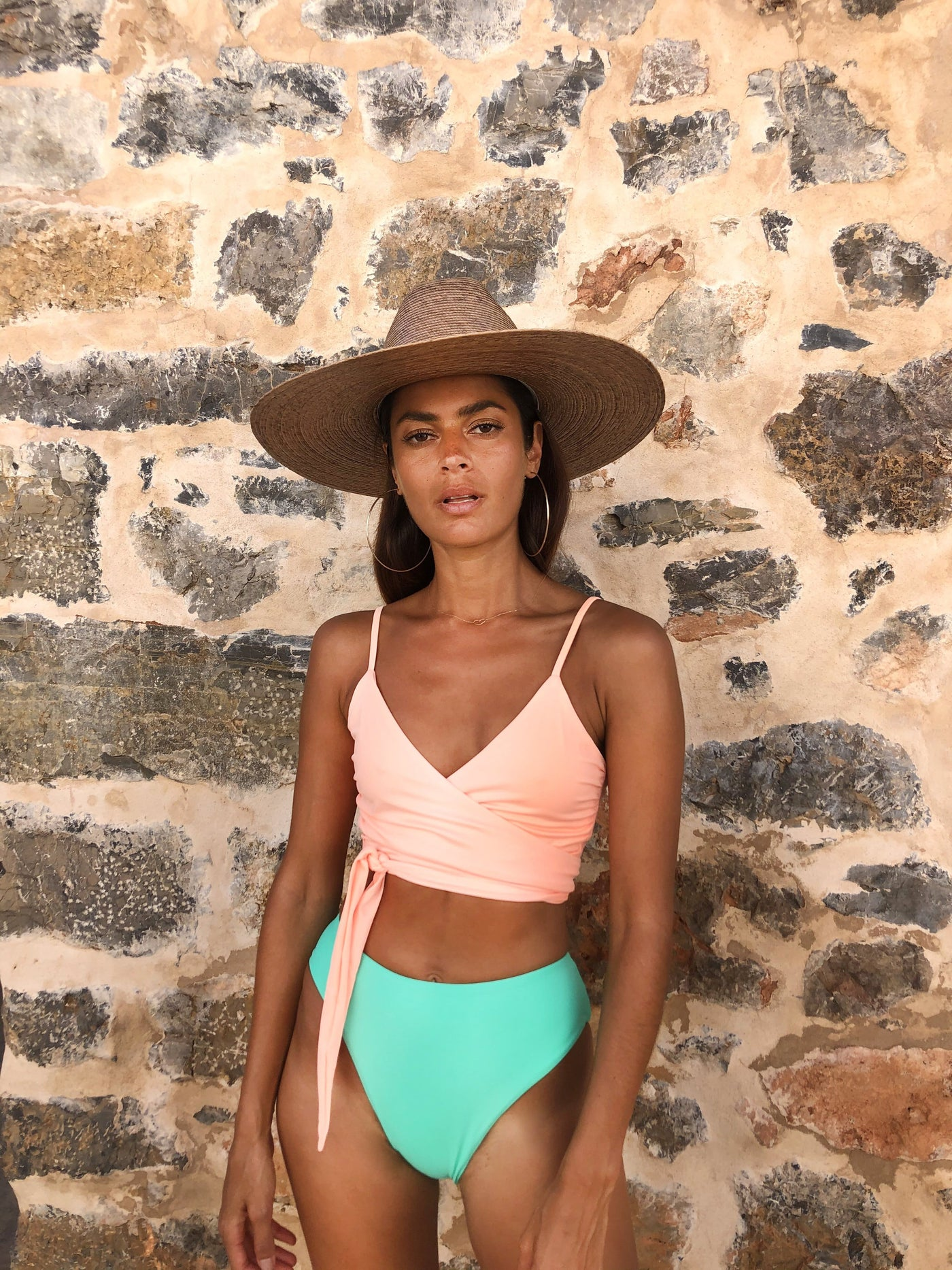Dancing Leopard model wearing Oyster Bikini Top in peach with aqua bottoms styled with straw sunhat against brick wall