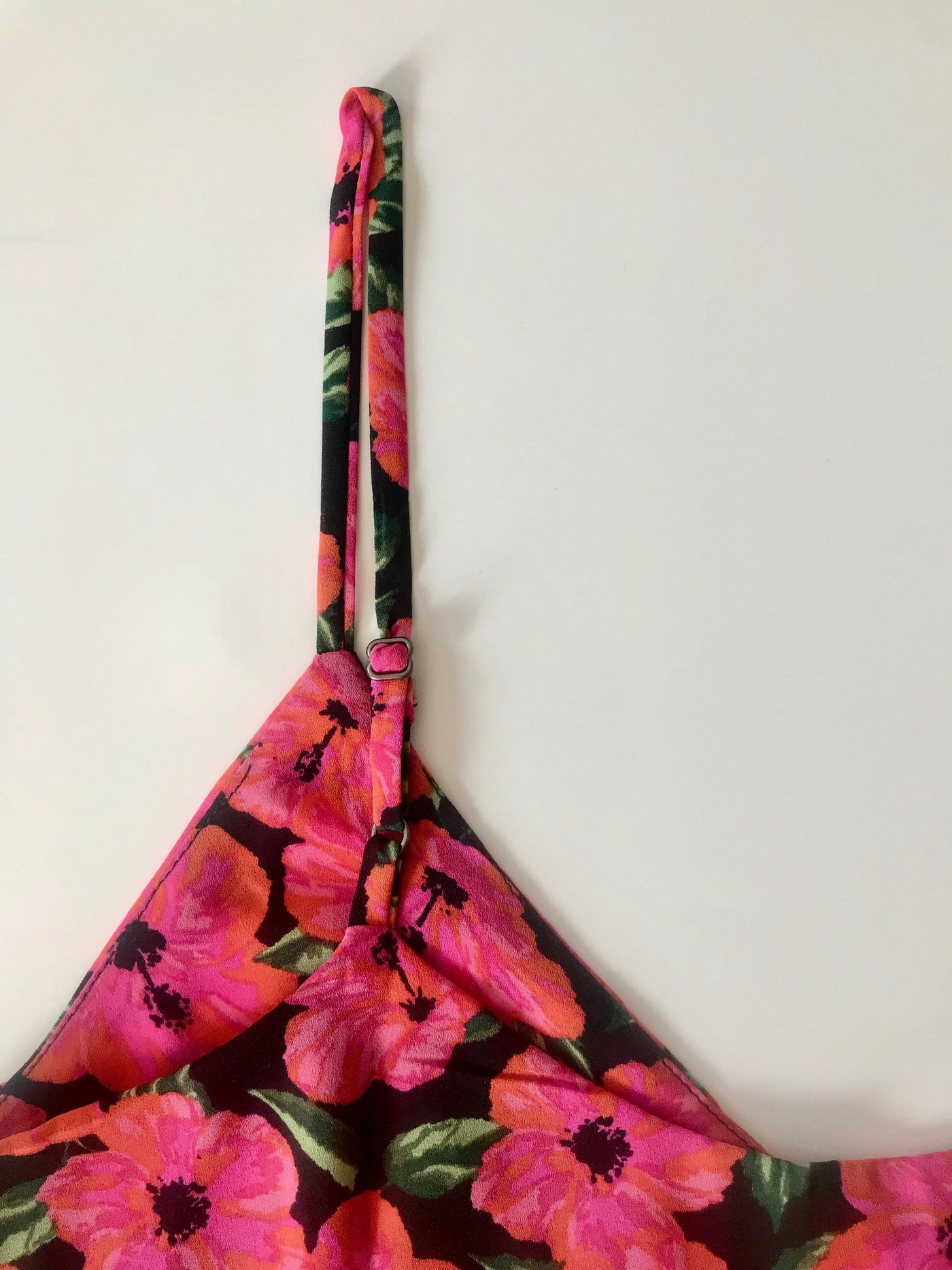 Close-up of Dancing Leopard Birdie Cami Top in pink hibiscus floral print strap on white background