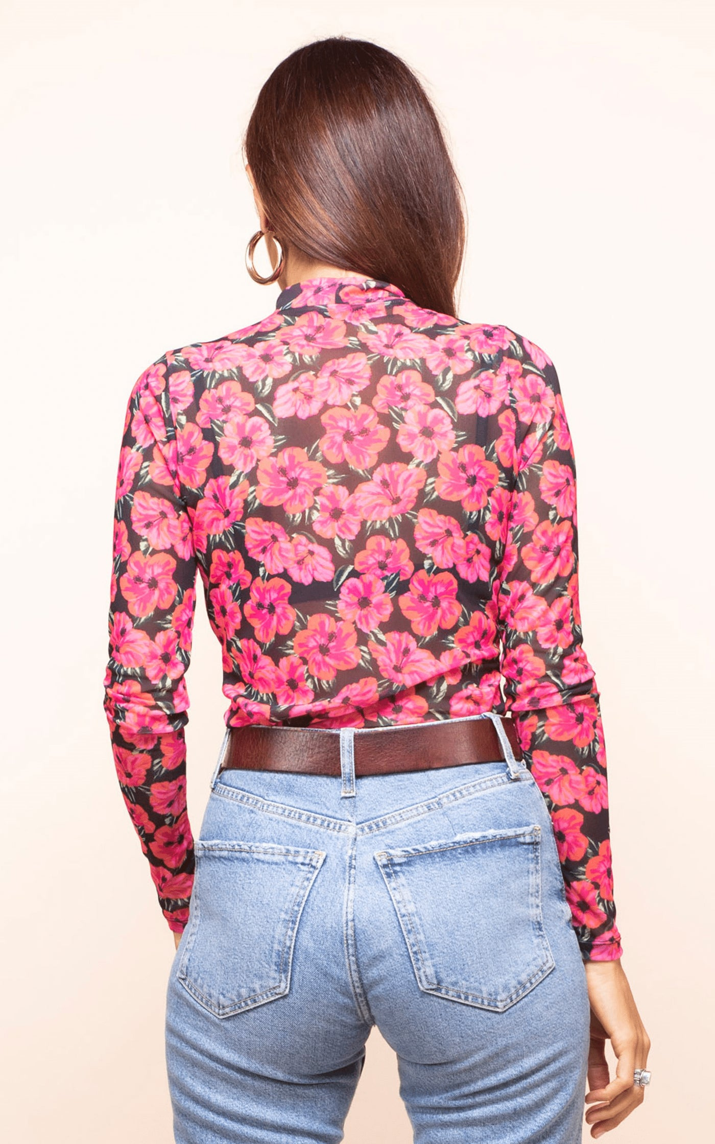 Backward-facing model wears Dancing Leopard Mitzi Frill Top in pink and black floral print