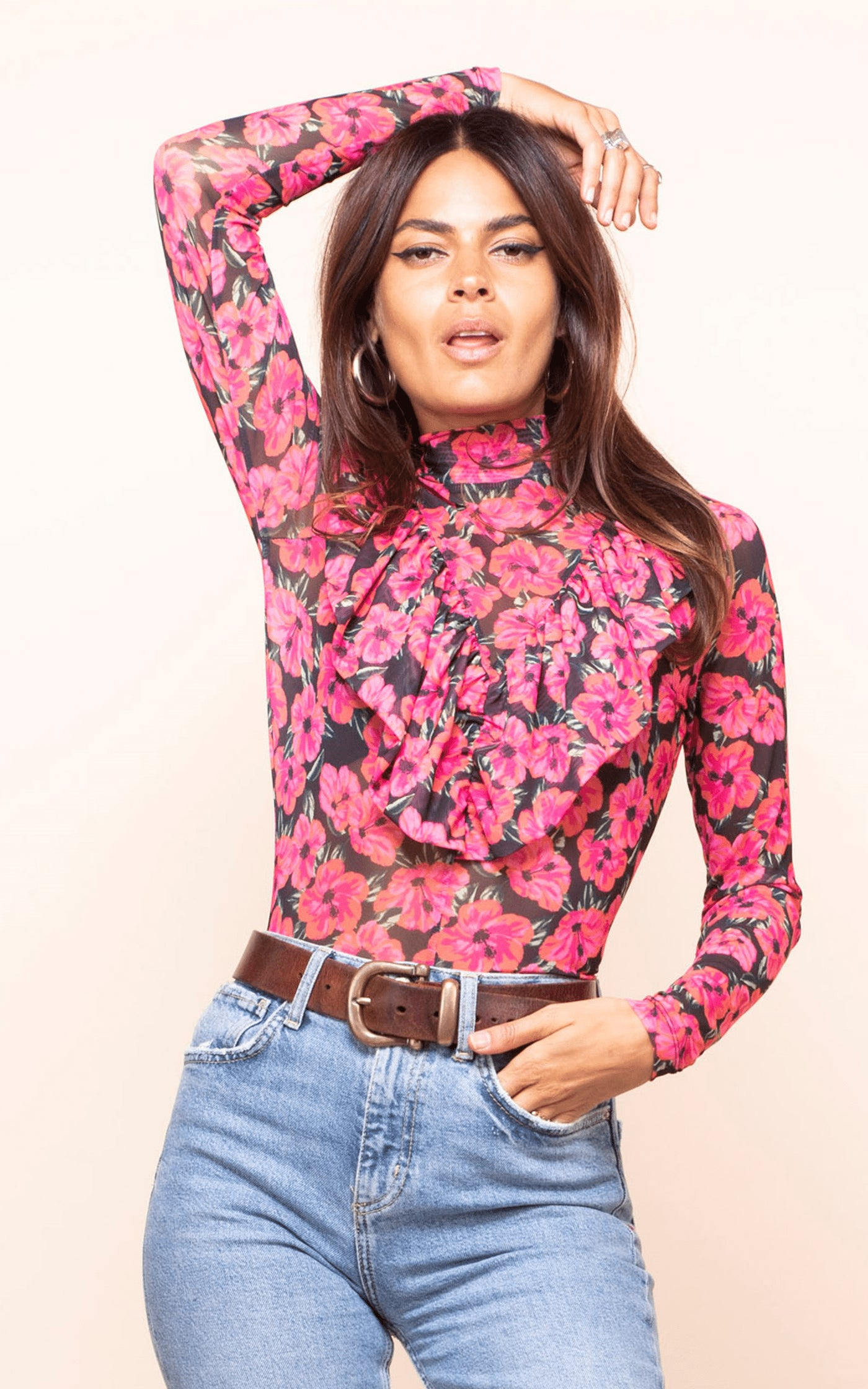 Dancing Leopard model faces forward with one arm above head wearing Mitzi Frill Top with jeans