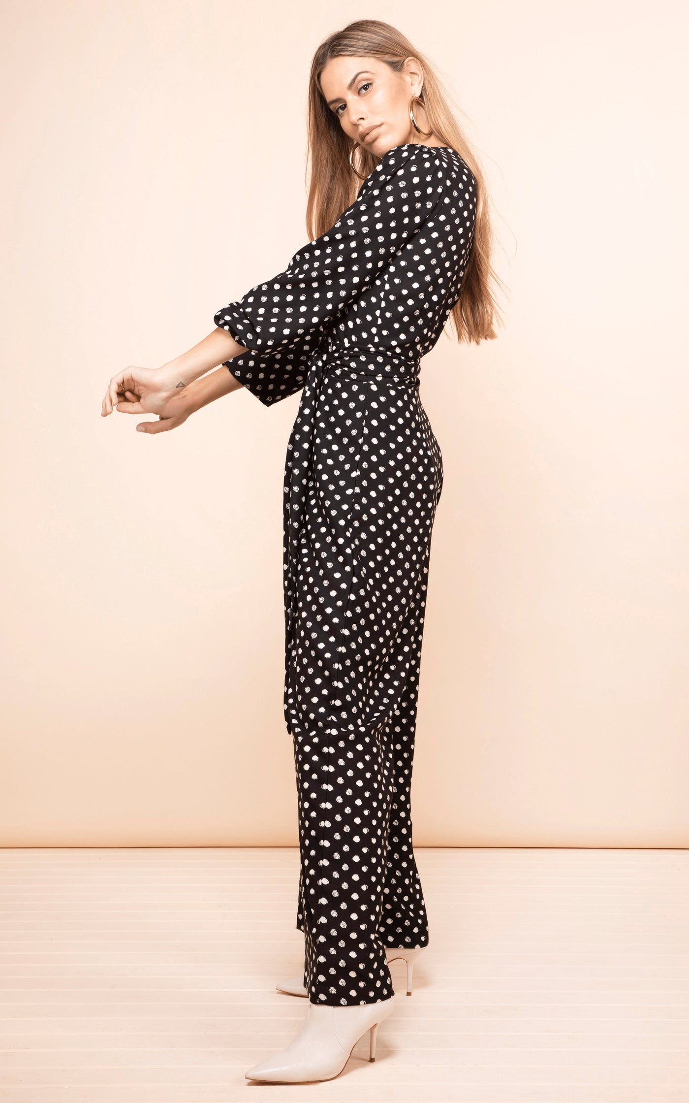 Sideways-facing model with arms raised wears Dancing Leopard Mossie Jumpsuit in black dotty