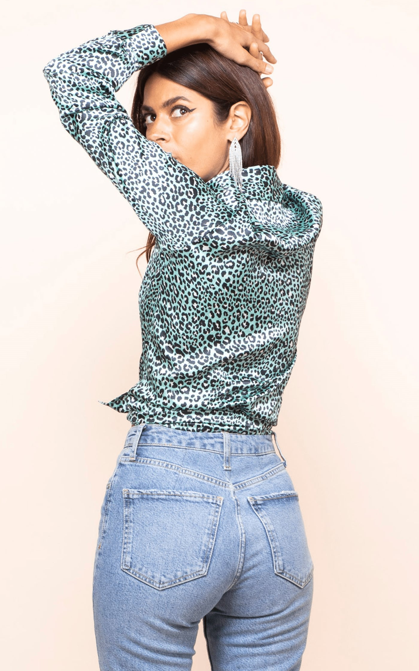 Dancing Leopard model turns backwards with arms up wearing Nevada Shirt in mint leopard print