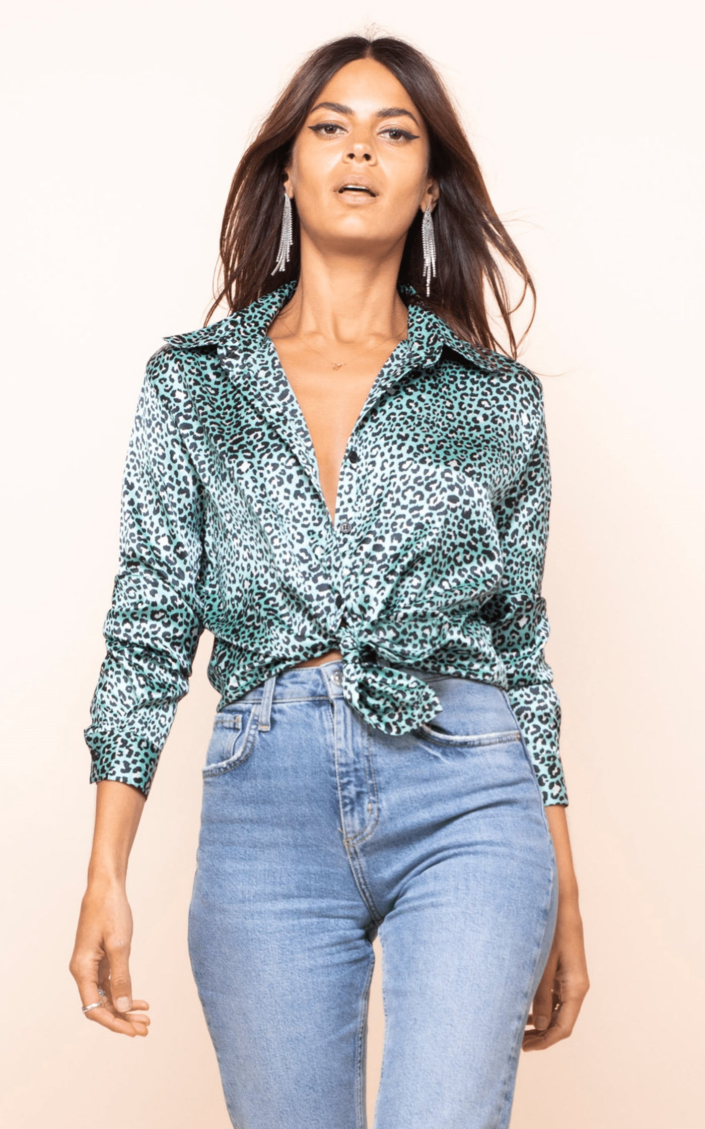 Dancing Leopard model walks forward wearing Nevada Shirt in mint ditzy leopard print with jeans