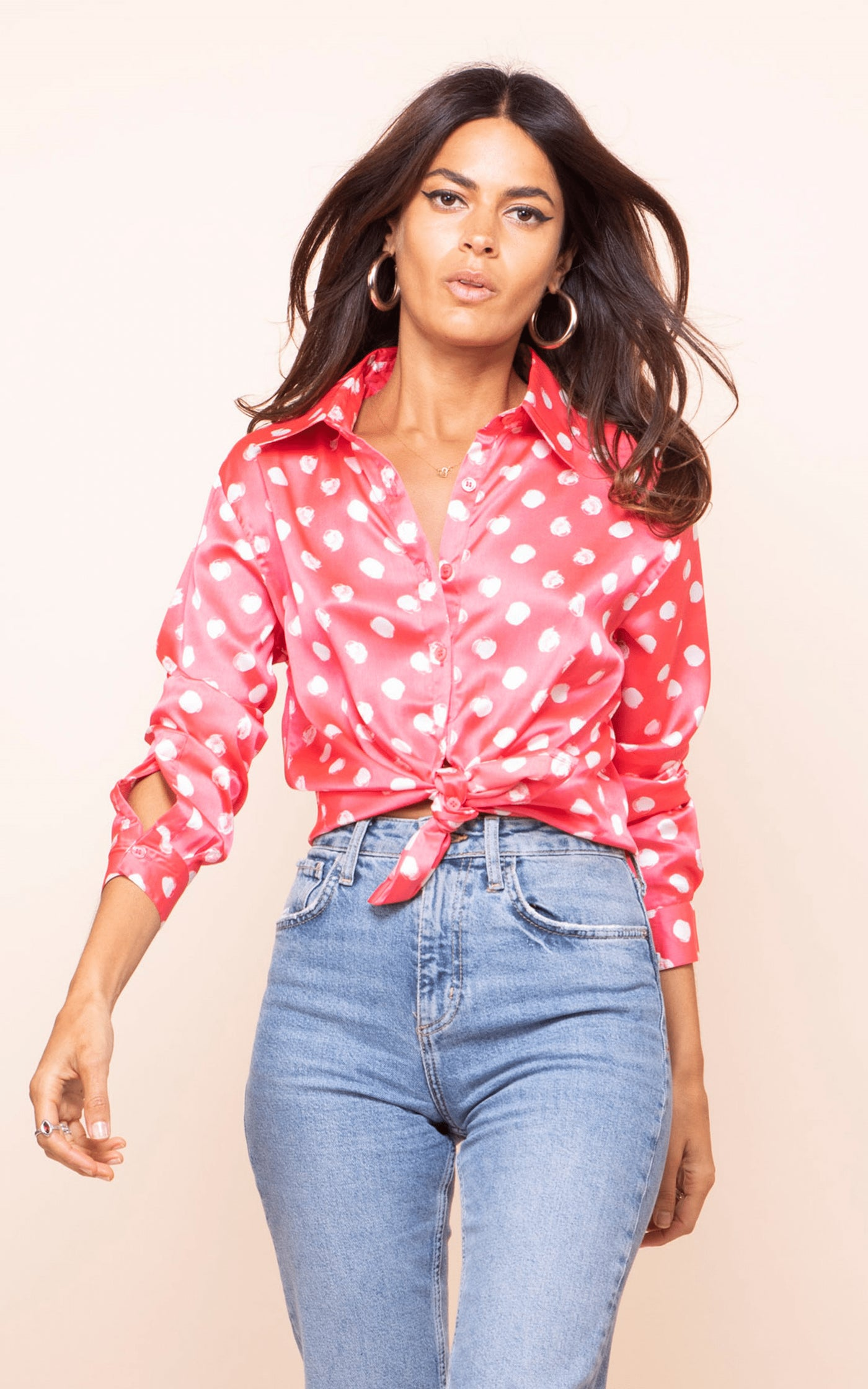 Dancing Leopard model walks forwards wearing Nevada Shirt in red dotty print with jeans
