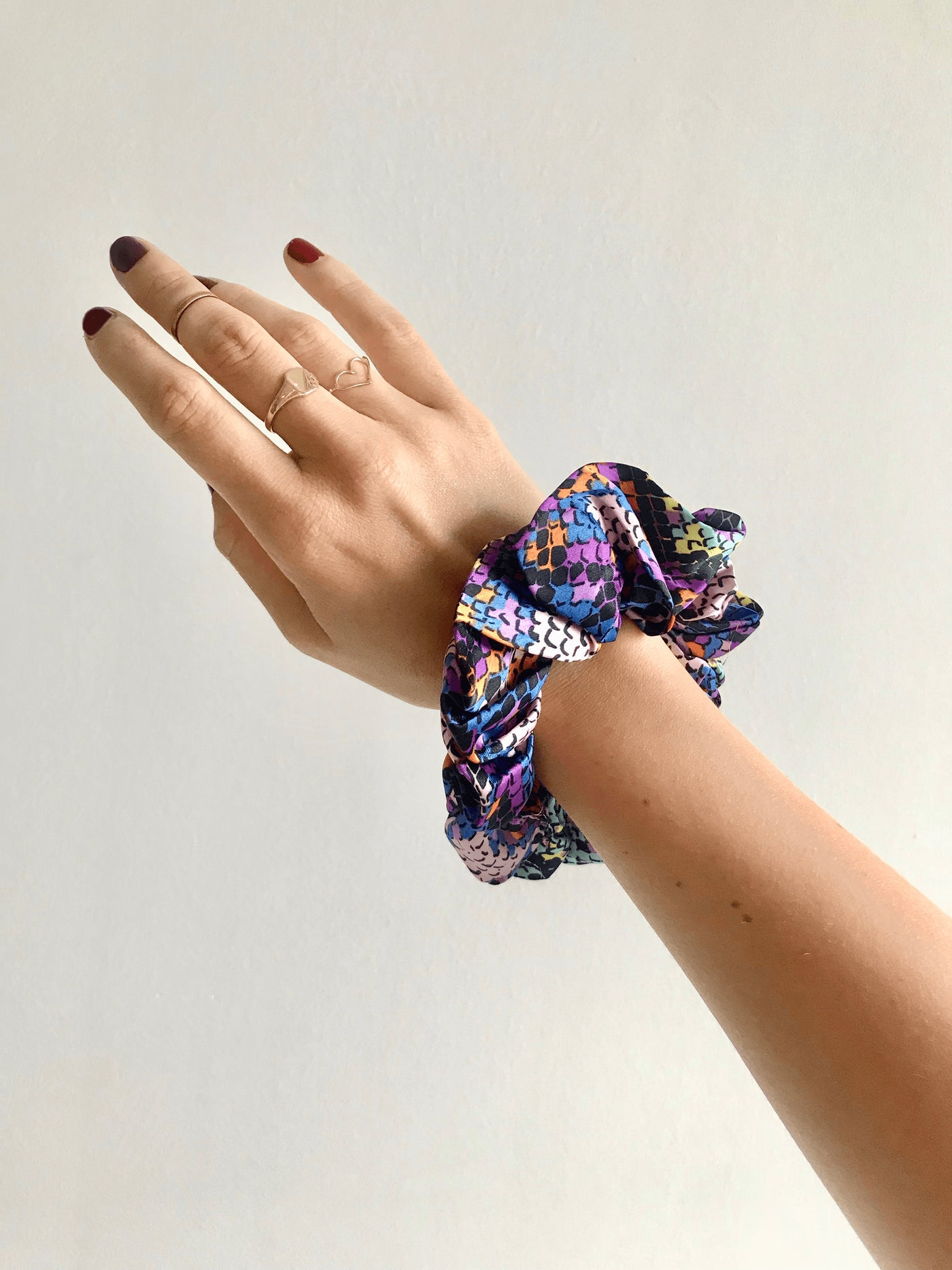 Dancing Leopard Multi Snake print scrunchie worn on wrist against white background