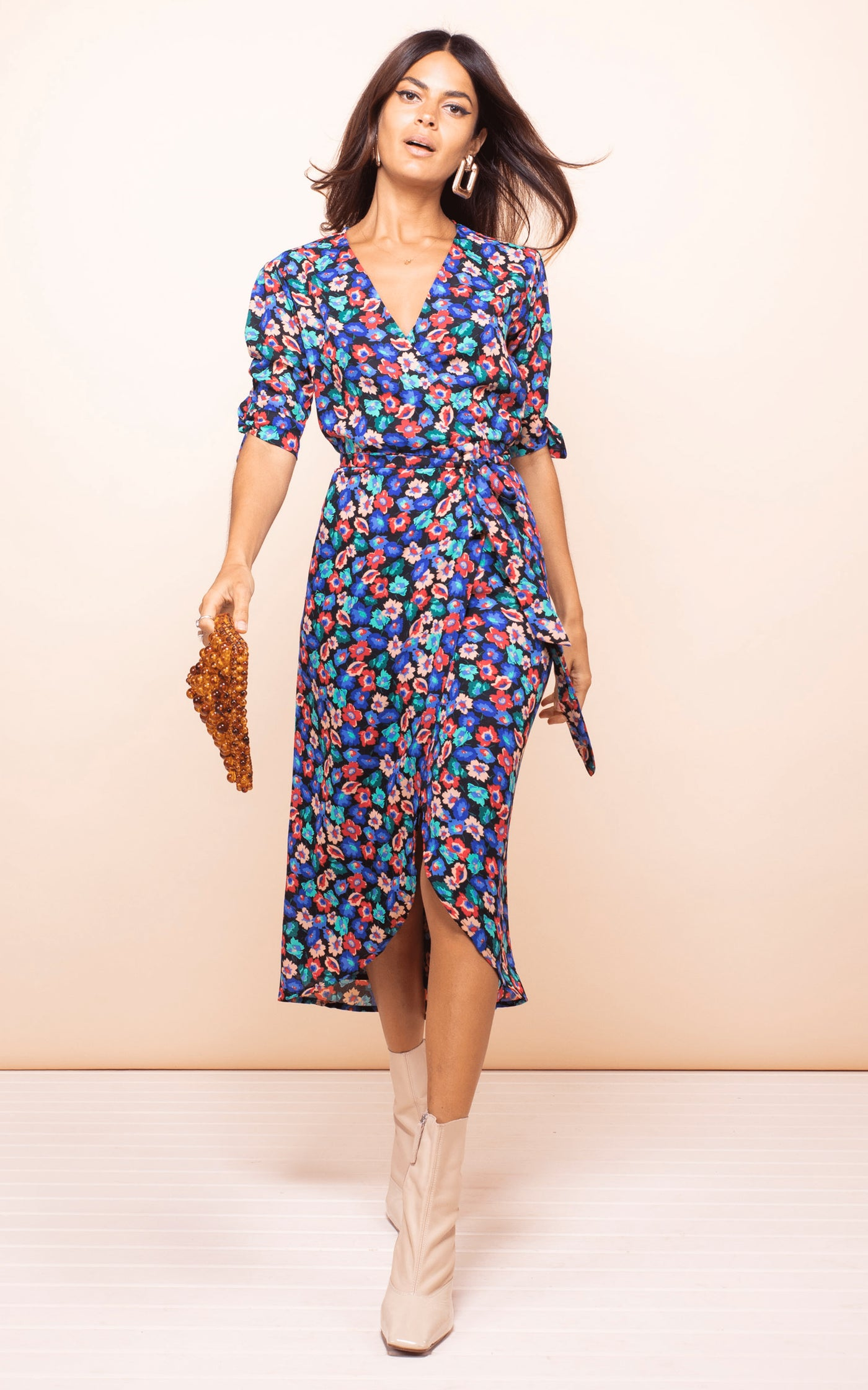 Model walks forwards wearing Dancing Leopard Olivera Midi Dress in floral print with white boots