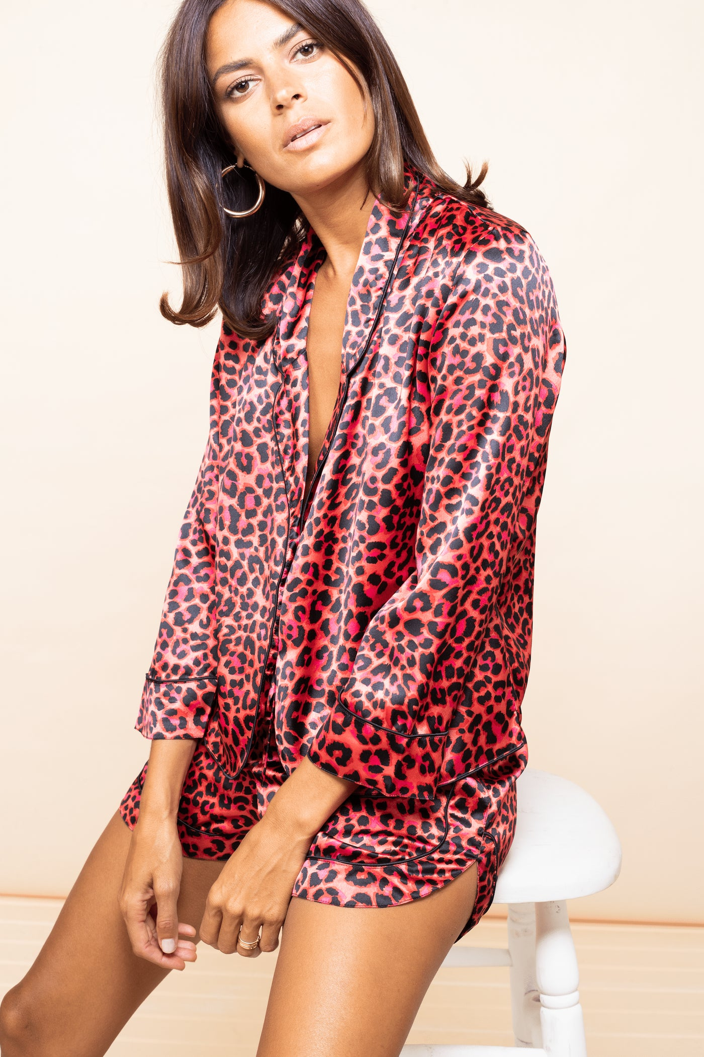 Dancing Leopard model sits on stool wearing Oona PJ Set in Red Leopard print