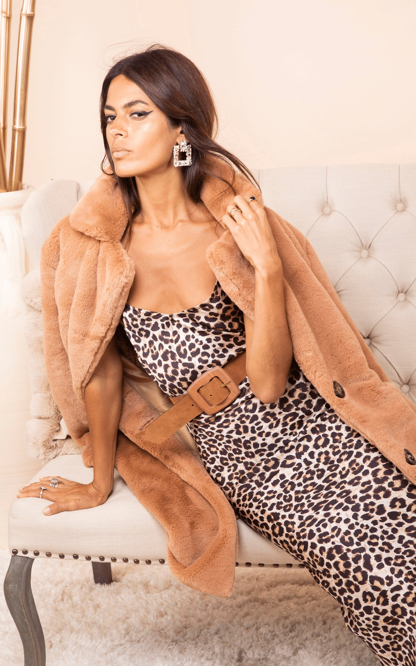 Model sits down wearing Dancing Leopard Paloma Maxi Slip Dress in leopard print and tan coat