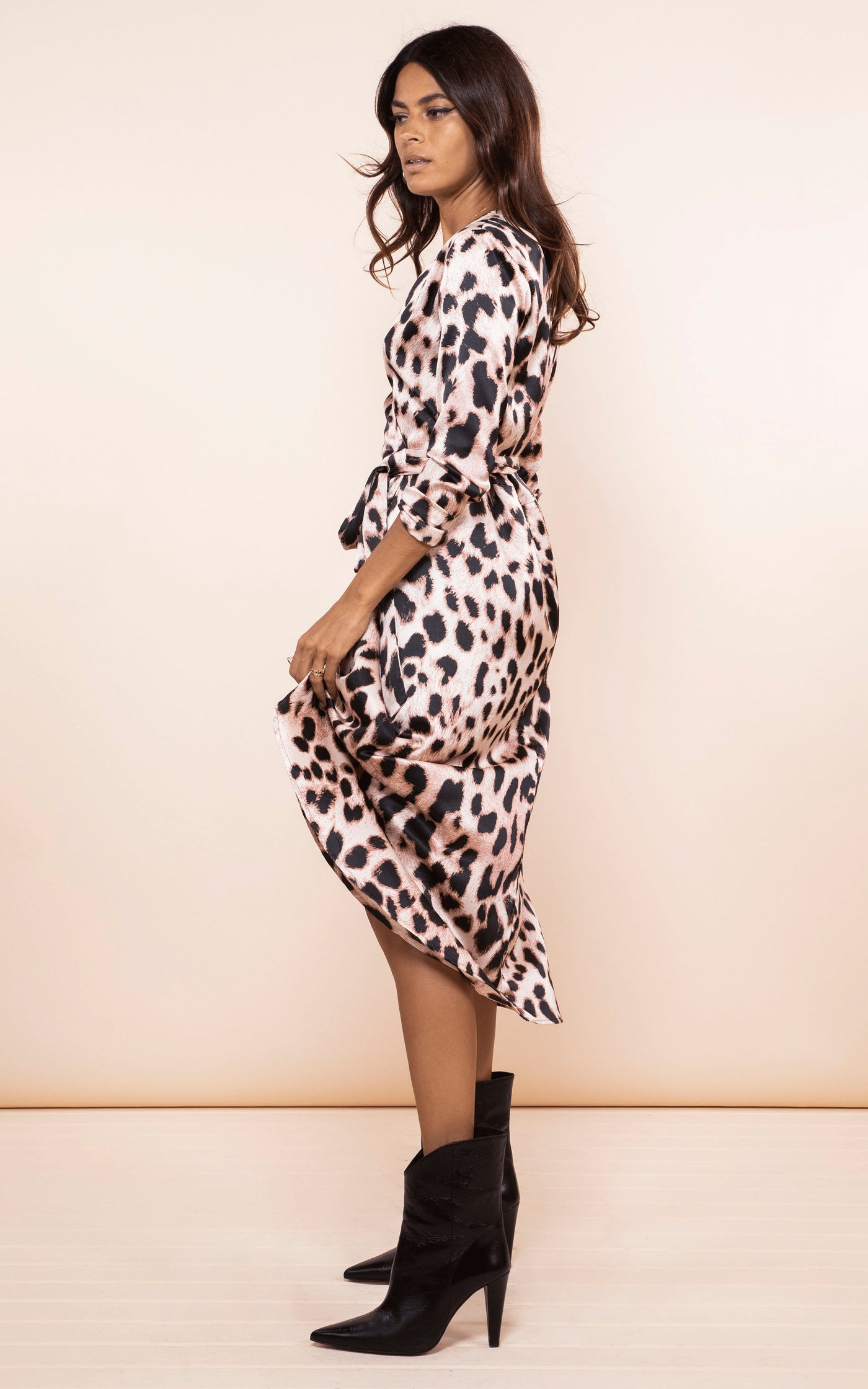 Dancing Leopard model stands sideways wearing Yondal Dress in blush leopard print with boots
