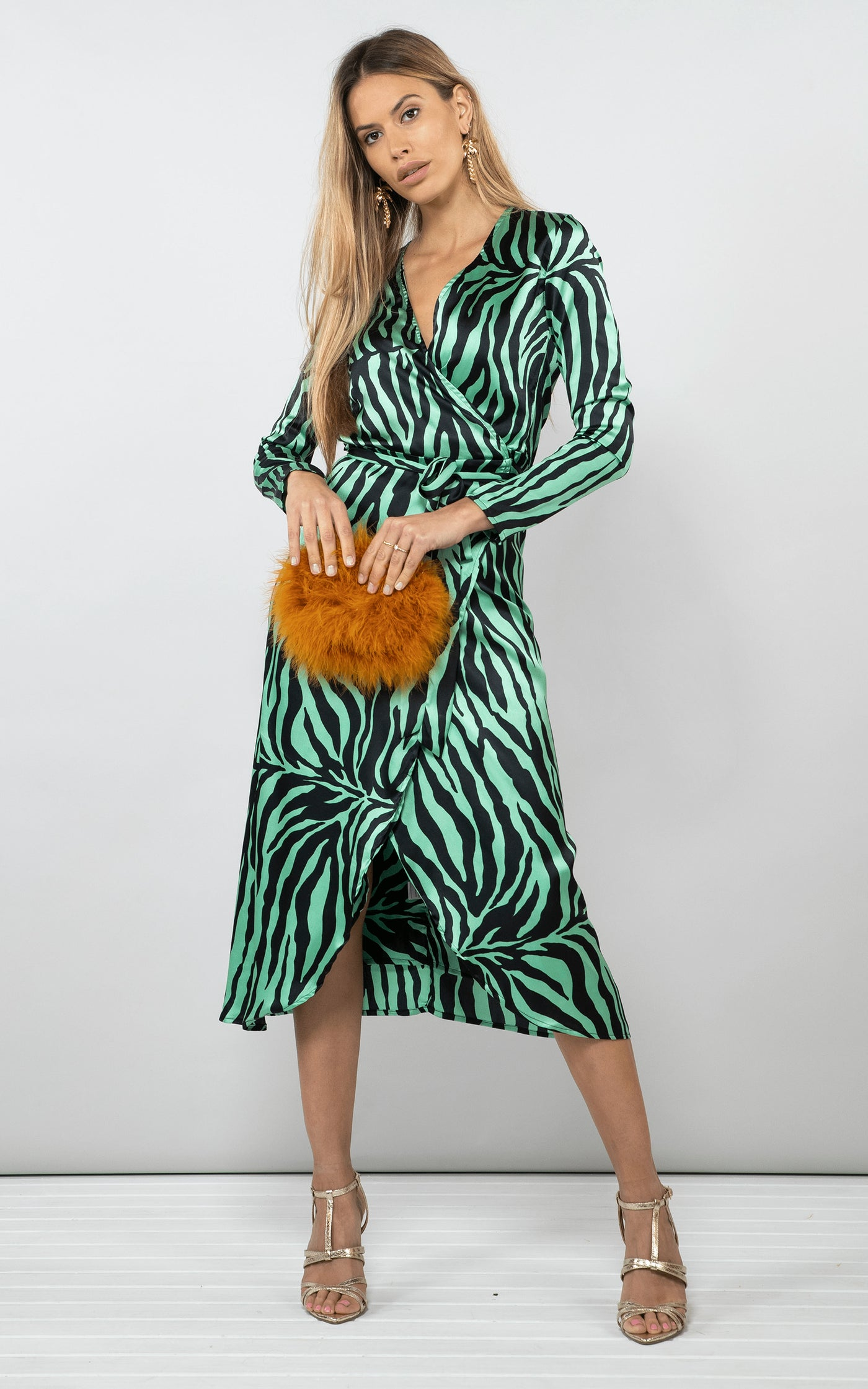 Dancing Leopard model faces forward holding handbag wearing Yondal Dress in green zebra print