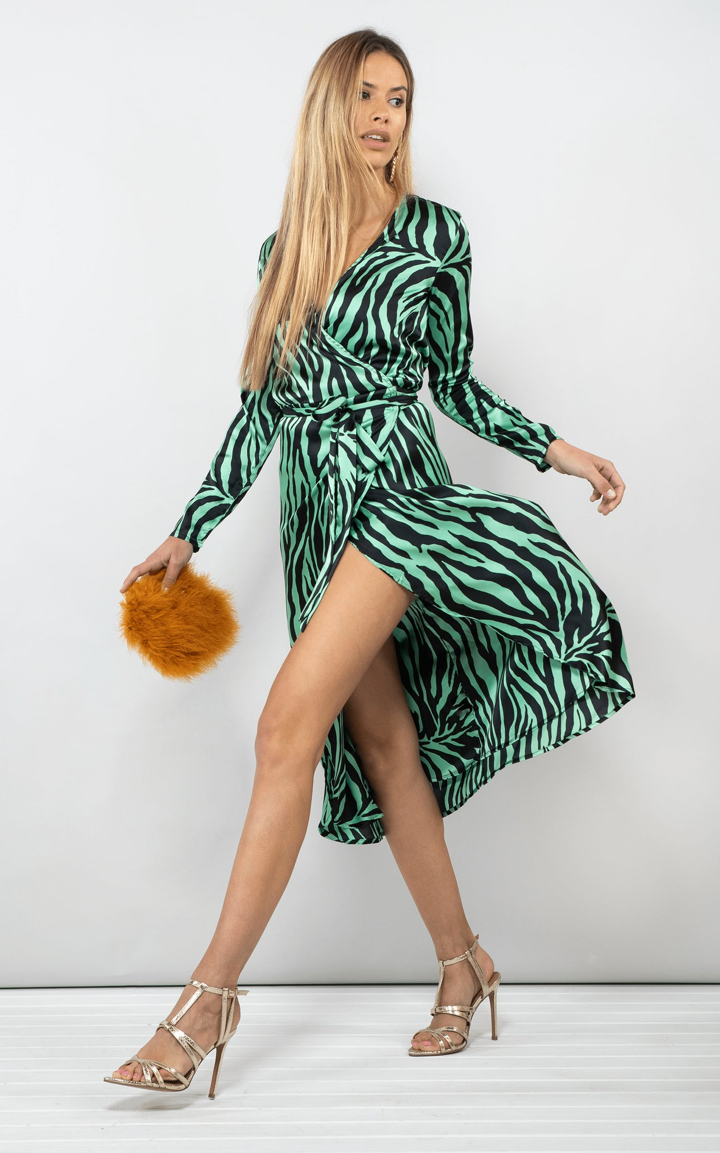 Dancing Leopard model walks forward holding handbag wearing Yondal Dress in green zebra print