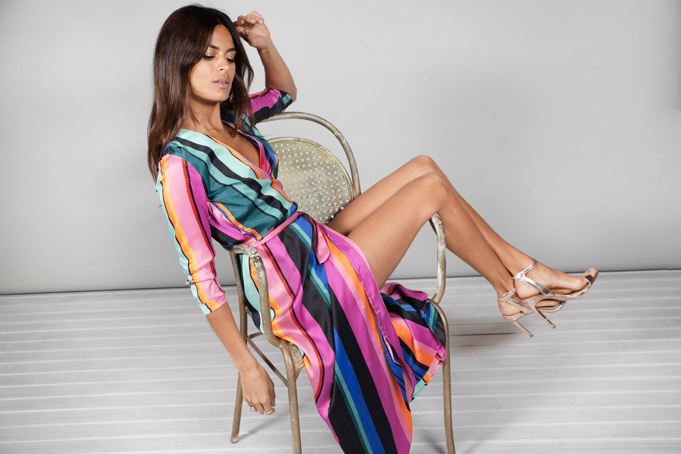 Dancing Leopard model reclines on sofa wearing Yondal Dress in stripe print with heels