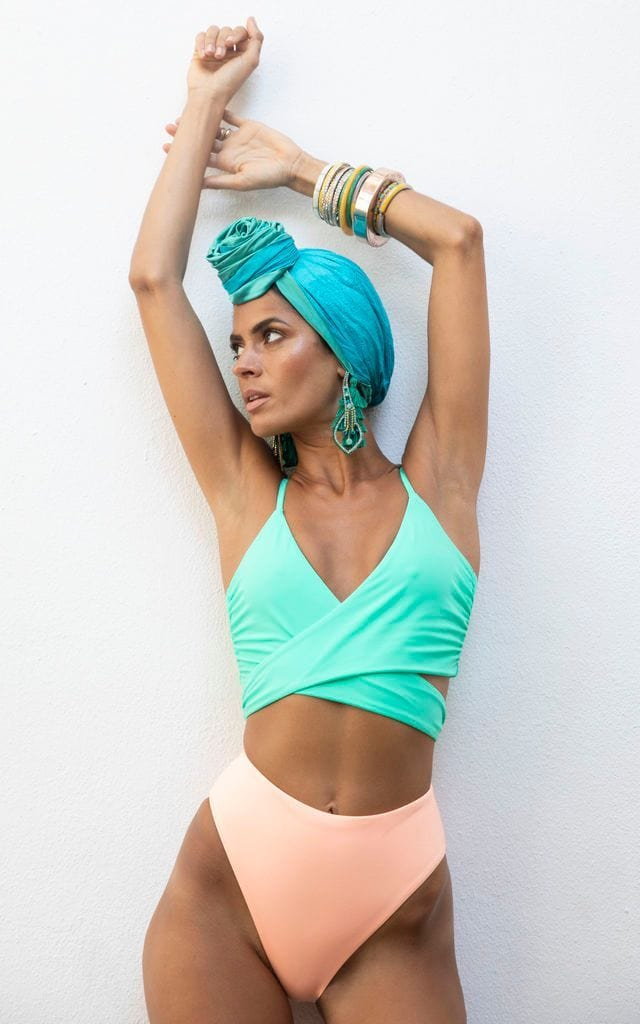 Dancing Leopard front-facing model with arm up wearing Calypso Bikini Bottom In Peach with blue turban