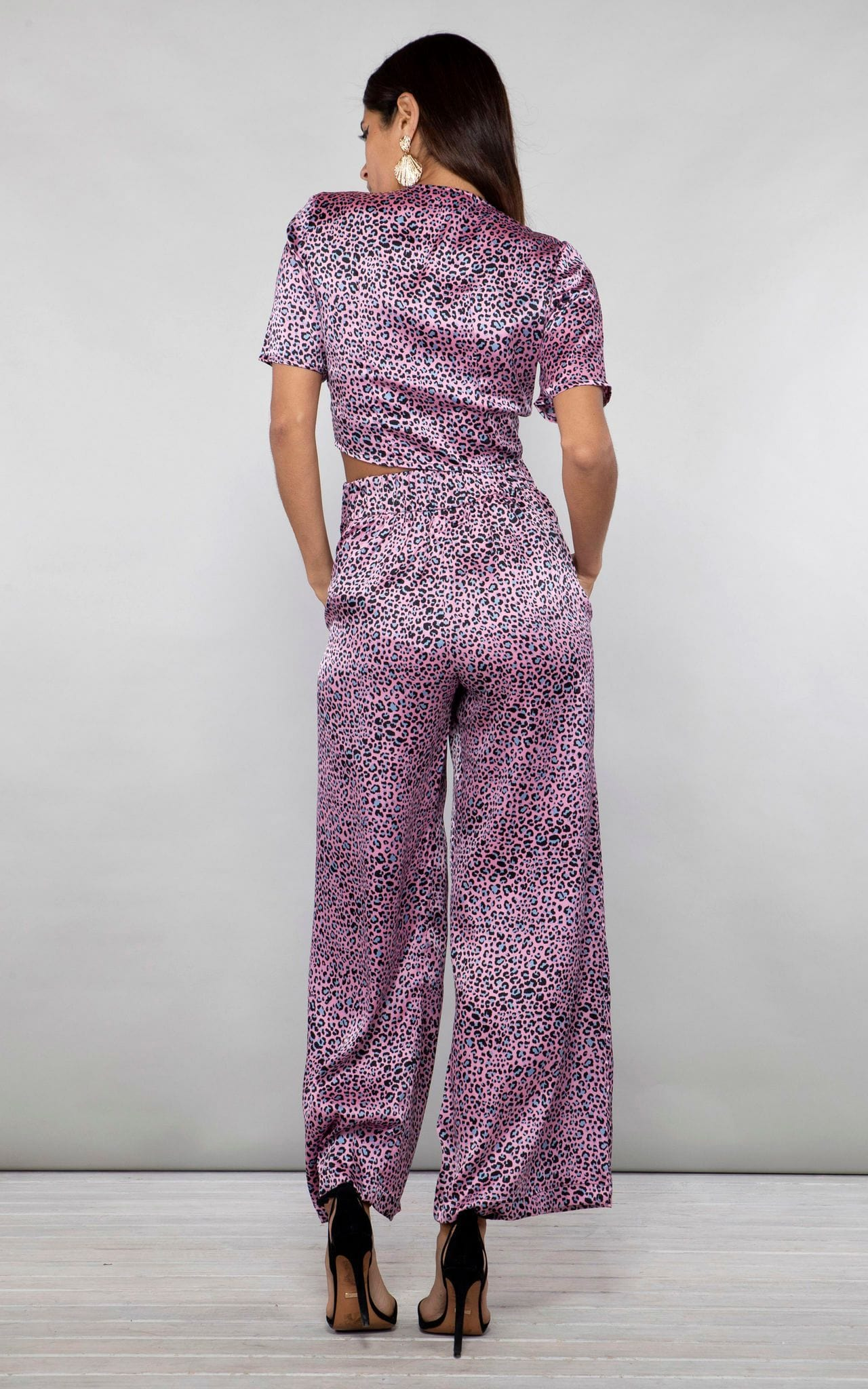 Backward-facing model with hands in pockets wears Chinchilla Trousers in pink leopard print