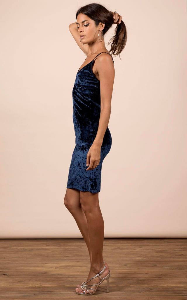 Dancing Leopard model faces sideways and holds hair up wearing Cici Mini Cami Dress in navy velvet