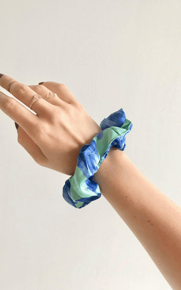 Dancing Leopard Blue Bloom print scrunchie worn on wrist against white background