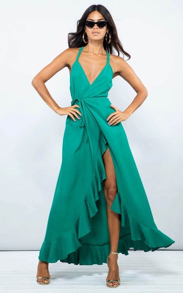 Front-facing model wears sunglasses and Dolce Vita Dress in emerald green by Dancing Leopard