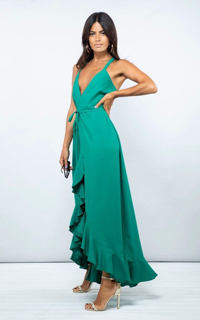 Side-facing model with hand on hip wears Dolce Vita Dress in emerald green by Dancing Leopard
