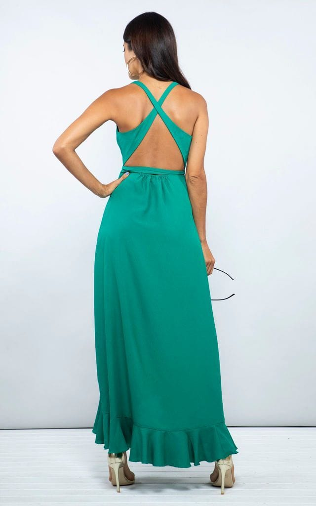 Backward-facing model with hand on hip wears Dolce Vita Dress in emerald green by Dancing Leopard
