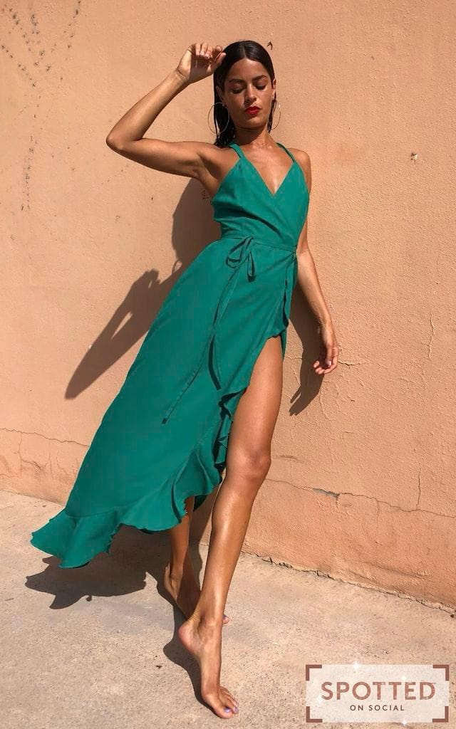 Dancing Leopard model leans against wall wearing Dolce Vita Dress in emerald green