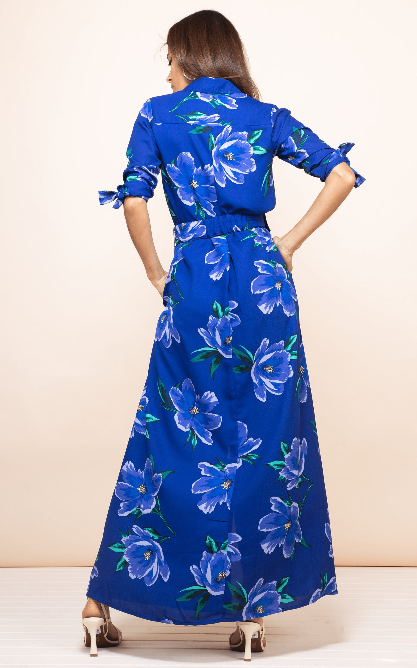 Model faces backwards with hands on hips wearing Dove Dress in blue floral print