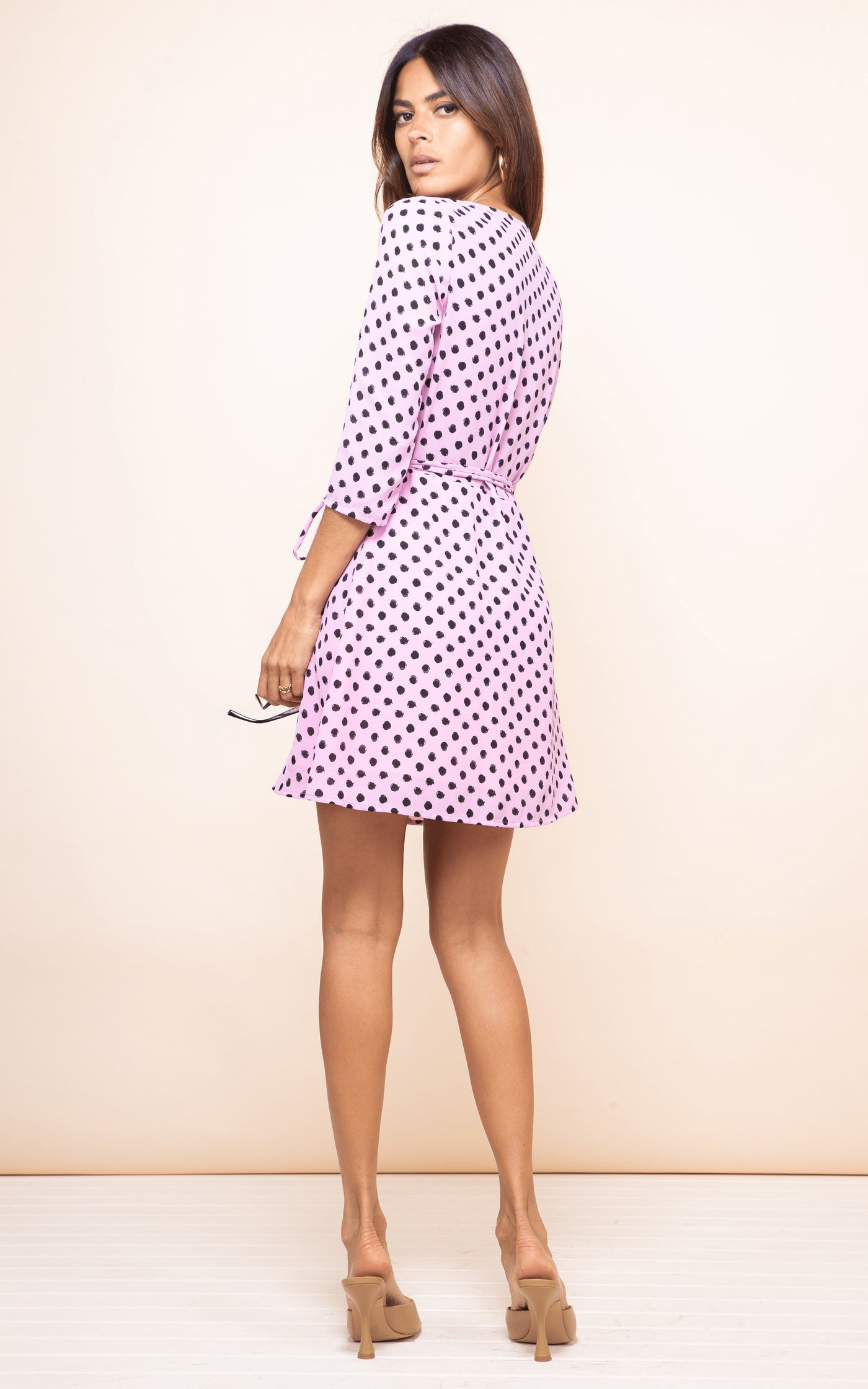Dancing Leopard model faces backwards and looks over shoulder wearing Teagan Dress in pink dotty print