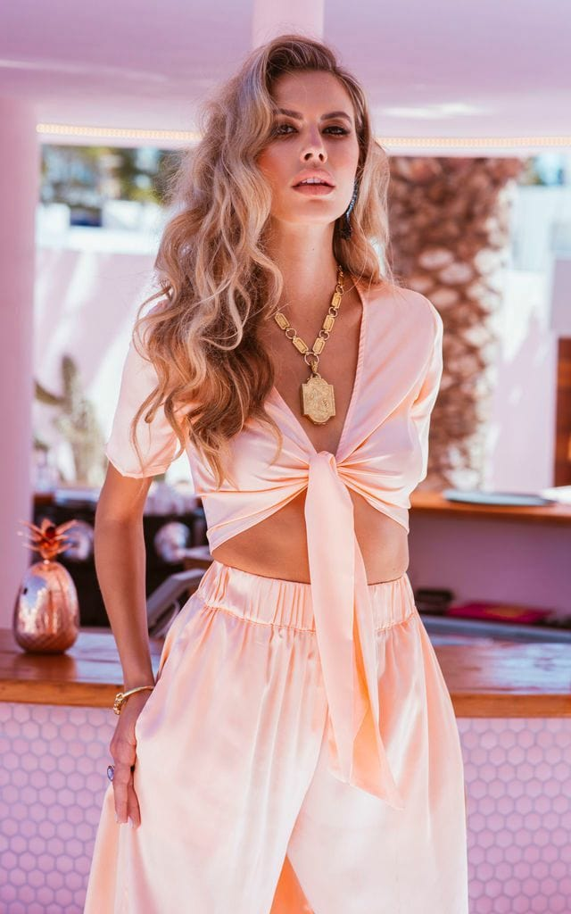 Dancing Leopard model faces forward wearing Gigi Wrap Top in peach with trousers and necklace