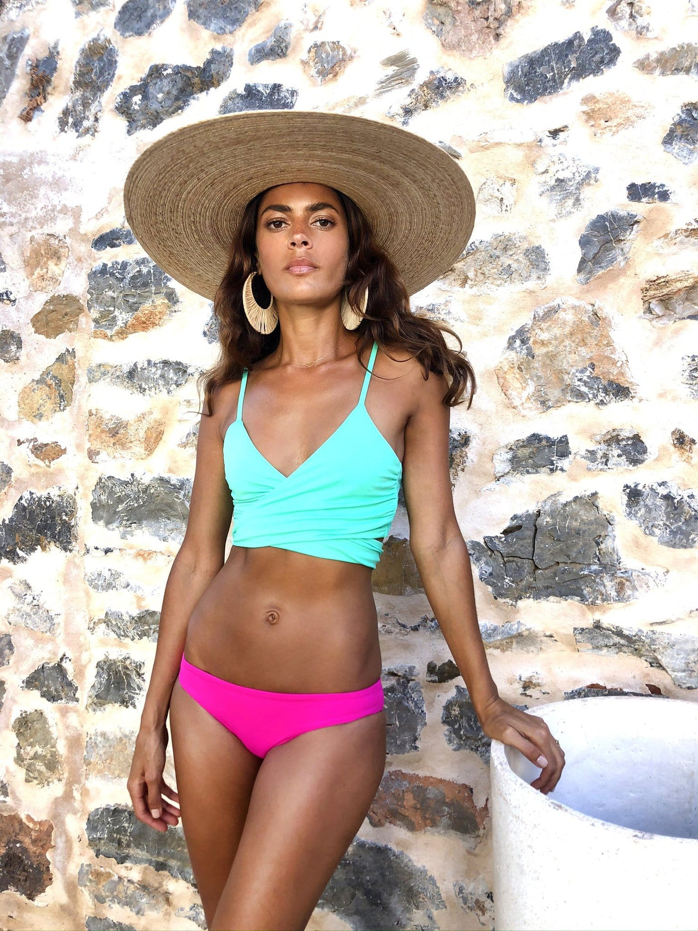 Forward facing Dancing Leopard model looks away wearing Oyster Bikini Top in aqua with magenta bottoms and straw hat